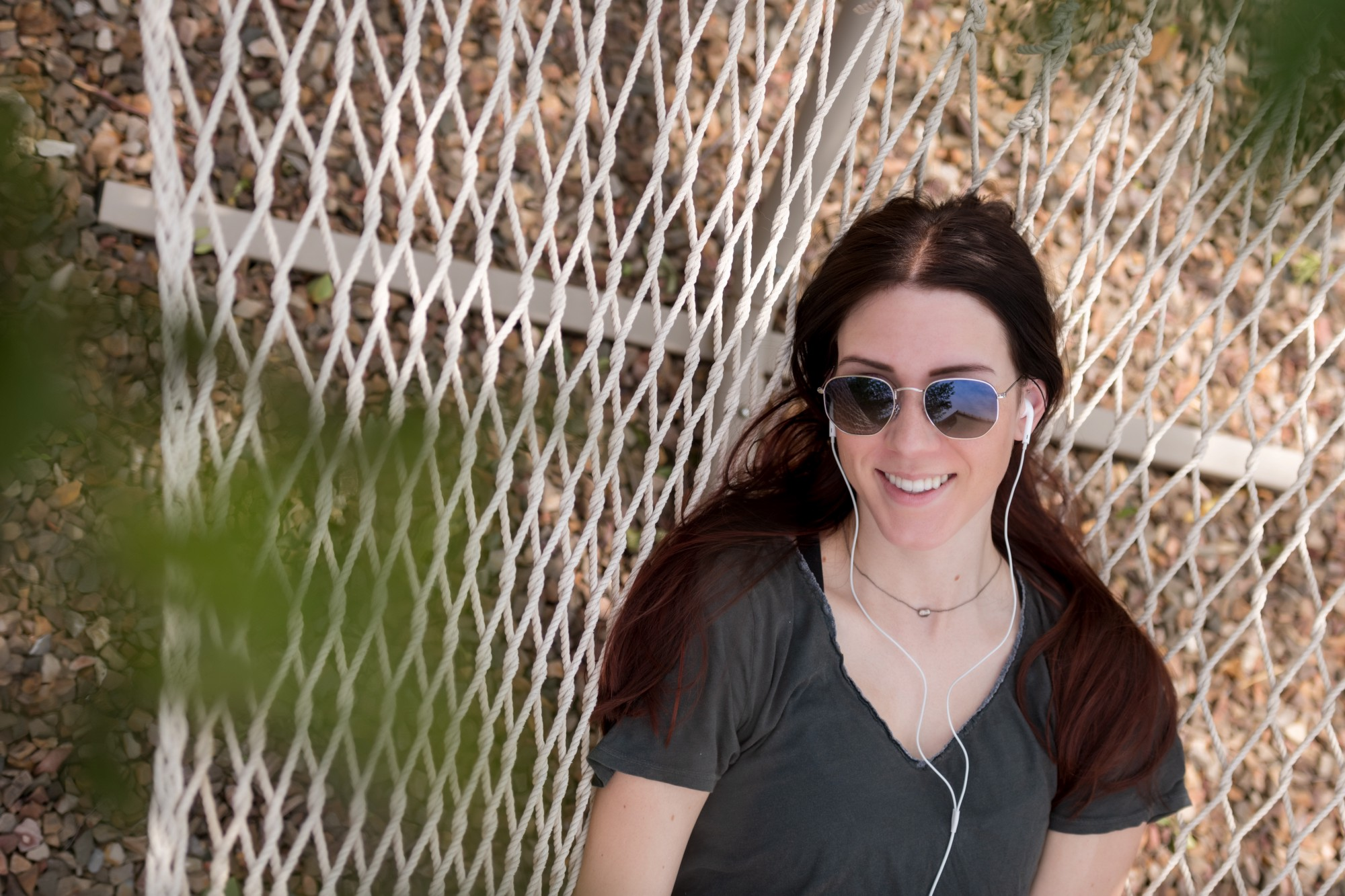A twenty-something' woman, with earbuds, smiles while lying in a hammock and looking up through tree branches.