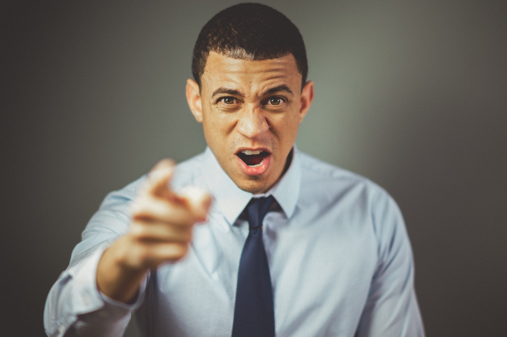 Angry Man in Tie Pointing at Camera