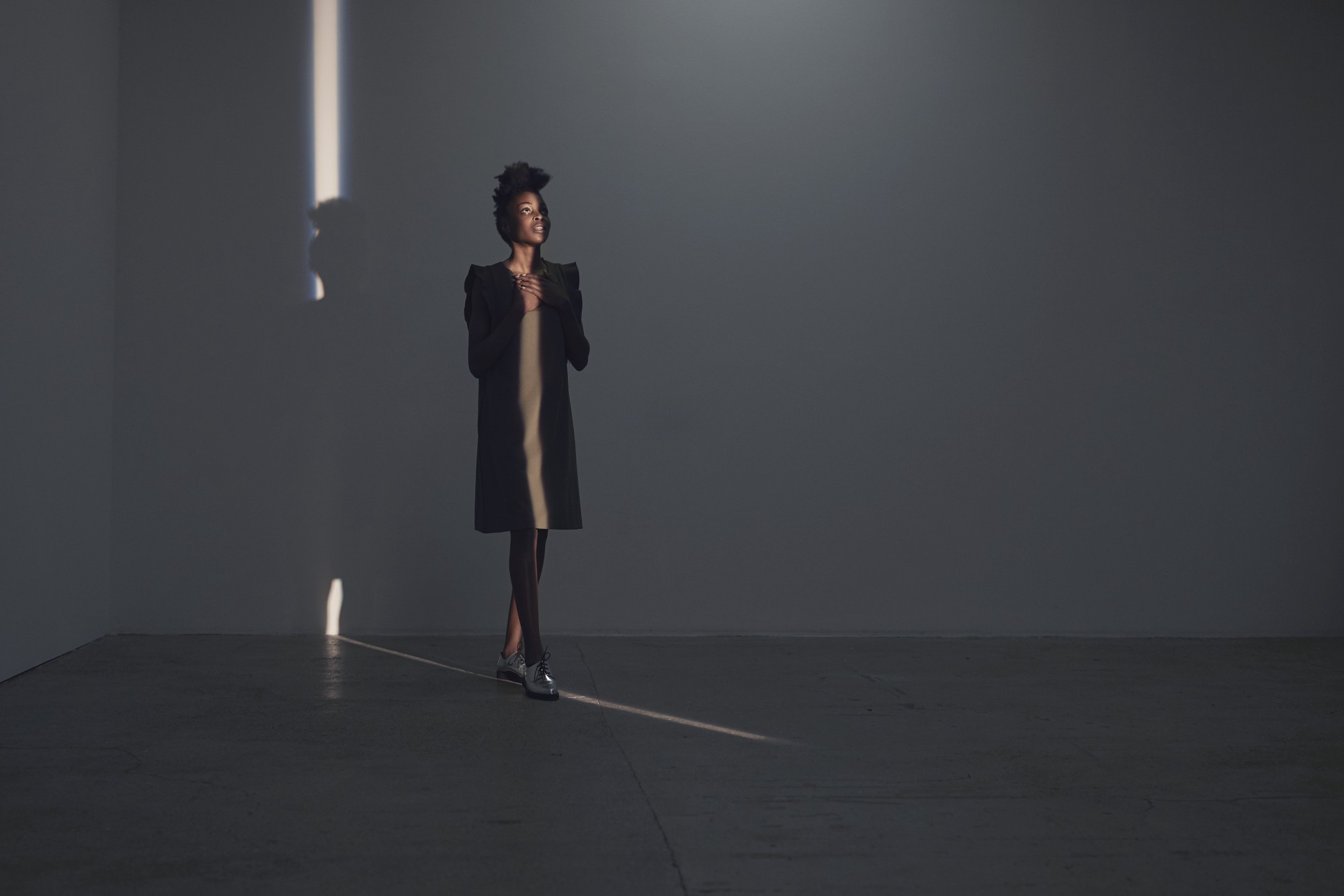 Woman walking in thin light stripe and looking up, in studio with concrete floor