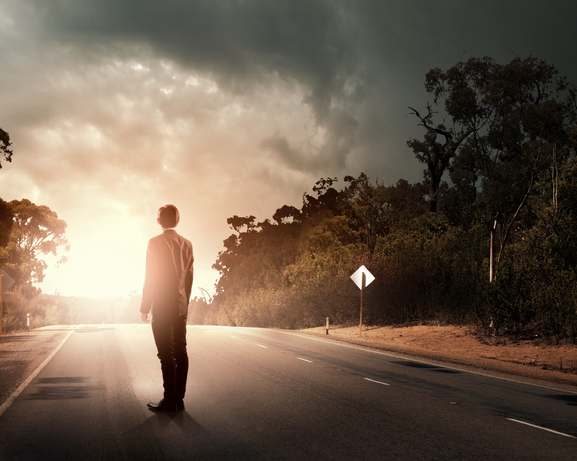 A man dressed in a suit stands on a road looking to the sunrise in the distance.
