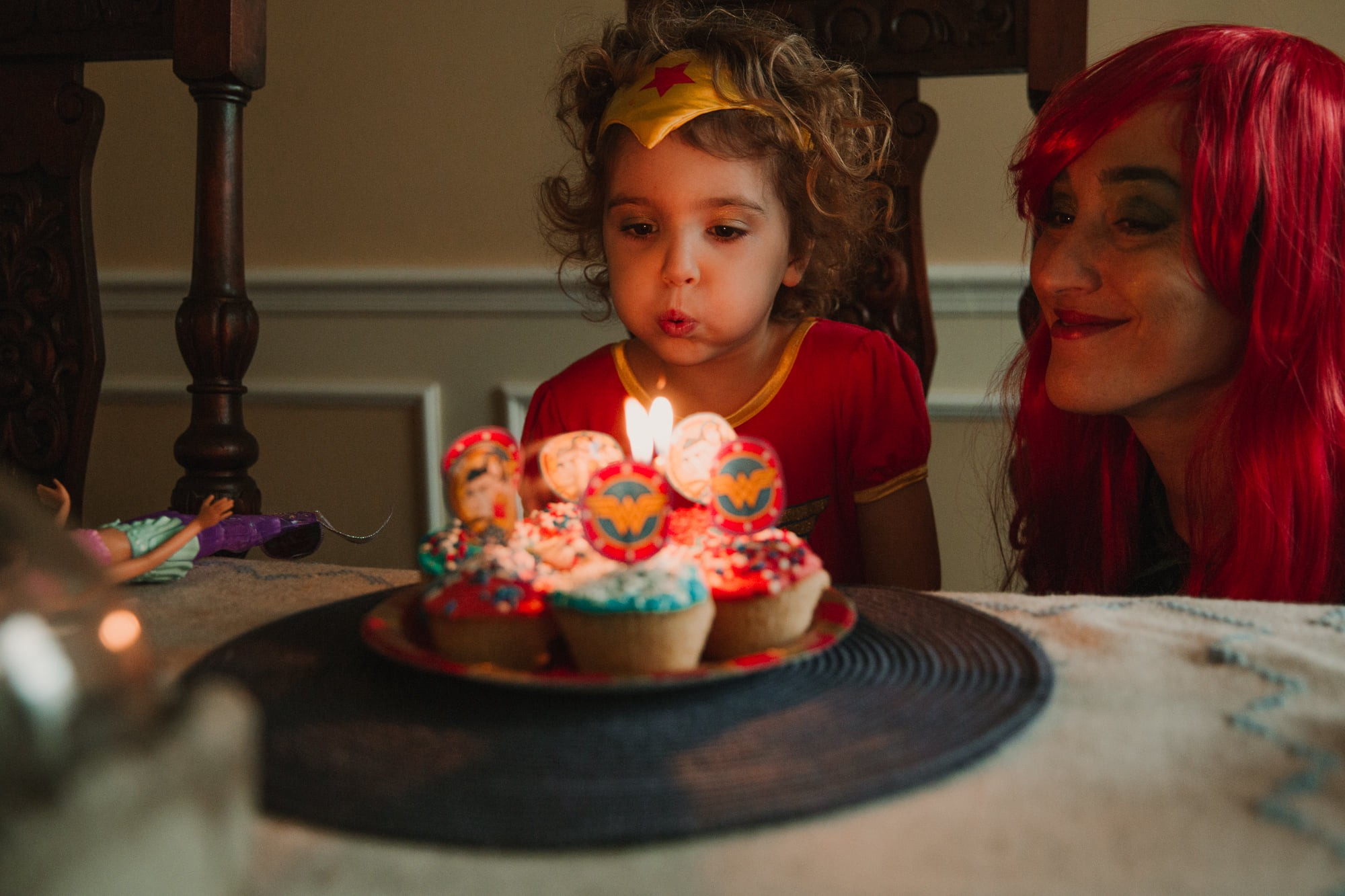 Little girl in a Wonder Woman costume blowing out candles on cupcakes. Mom in a shiny red wig crouched beside her, looking on