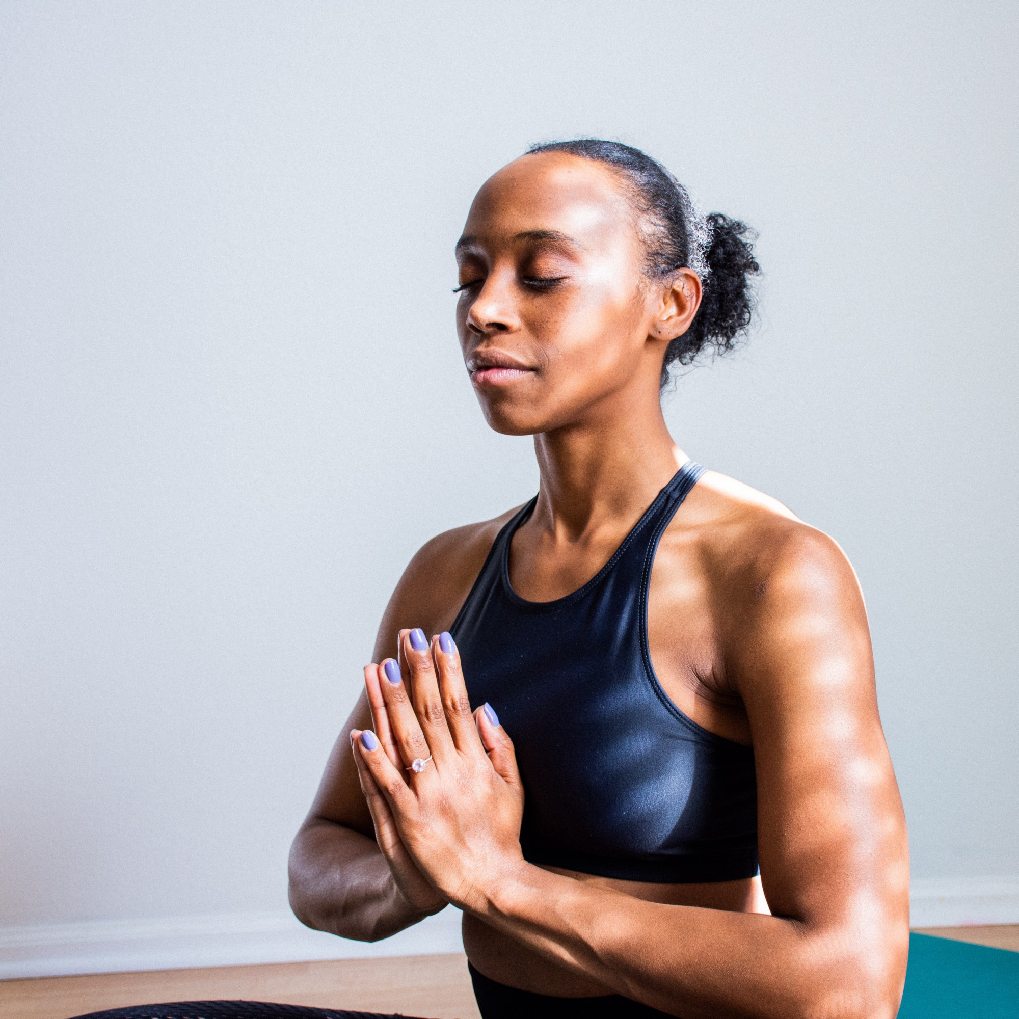 Woman sitting cross legged, meditating, with palms together, fingers pointing upwards, in front of chest.