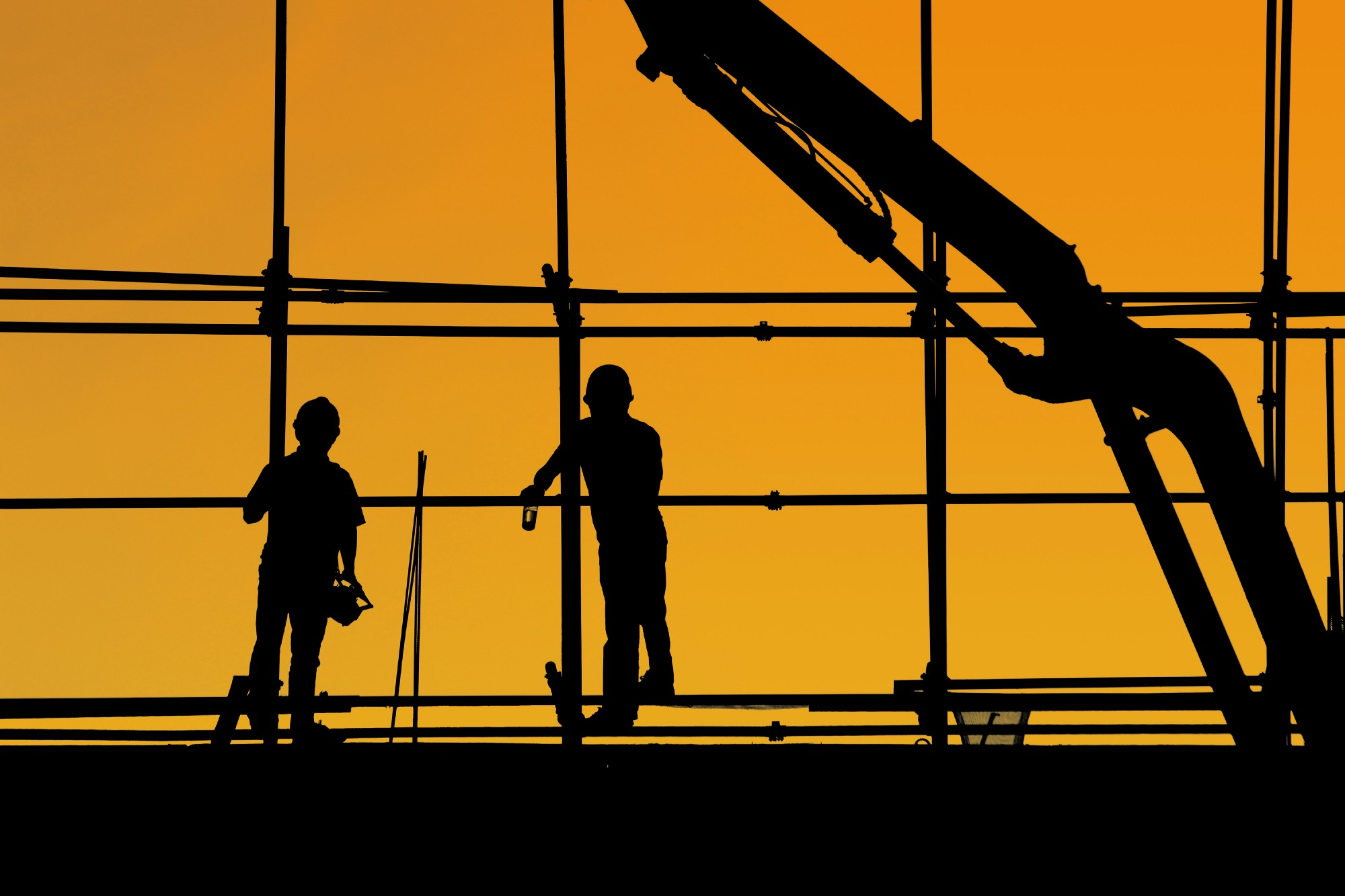 Silhouette of two construction workers on a scaffold