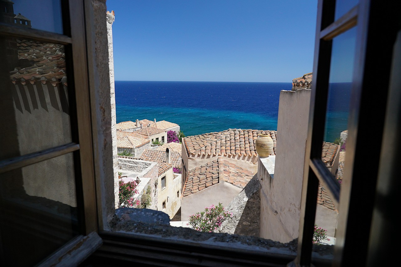 A window looking out on Greek rooftops and the blue  sea