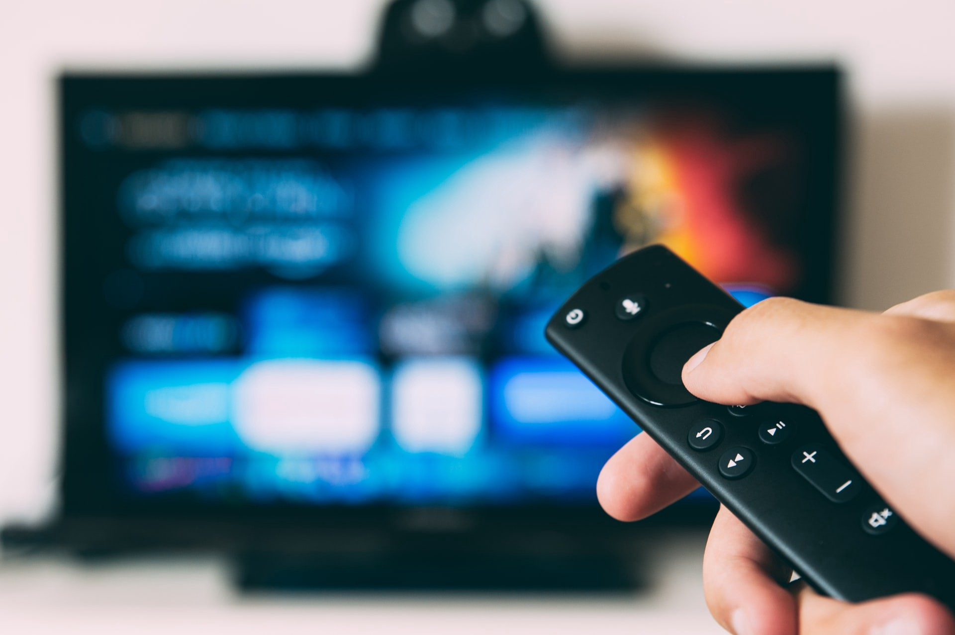 Hand holding a remote in front of a flat screen TV in the background.