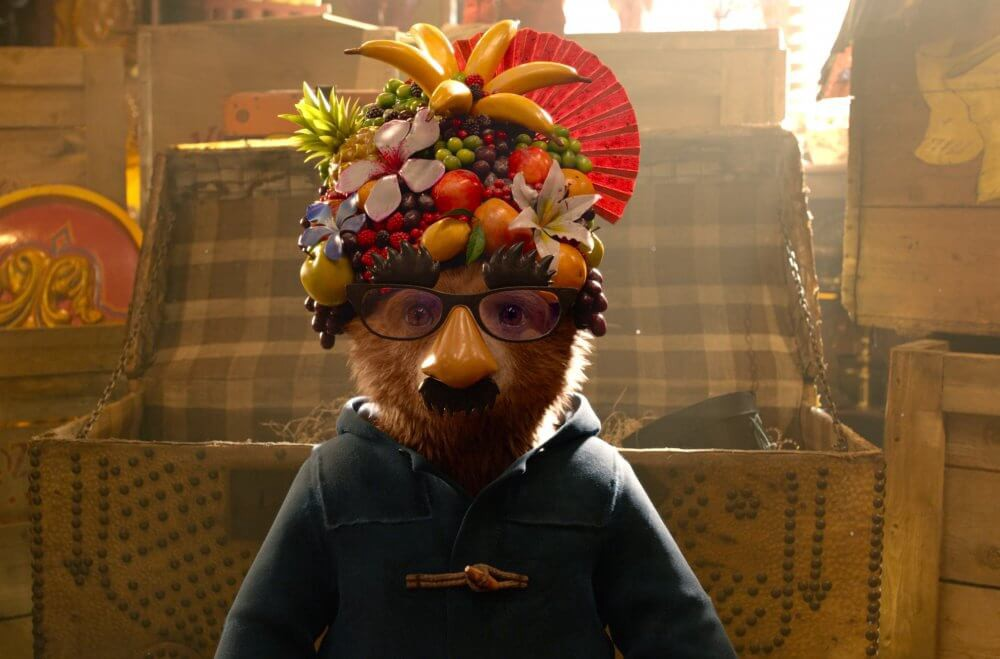 Paddington wearing an assortment of fruit on his head, glasses, and a fake moustache.