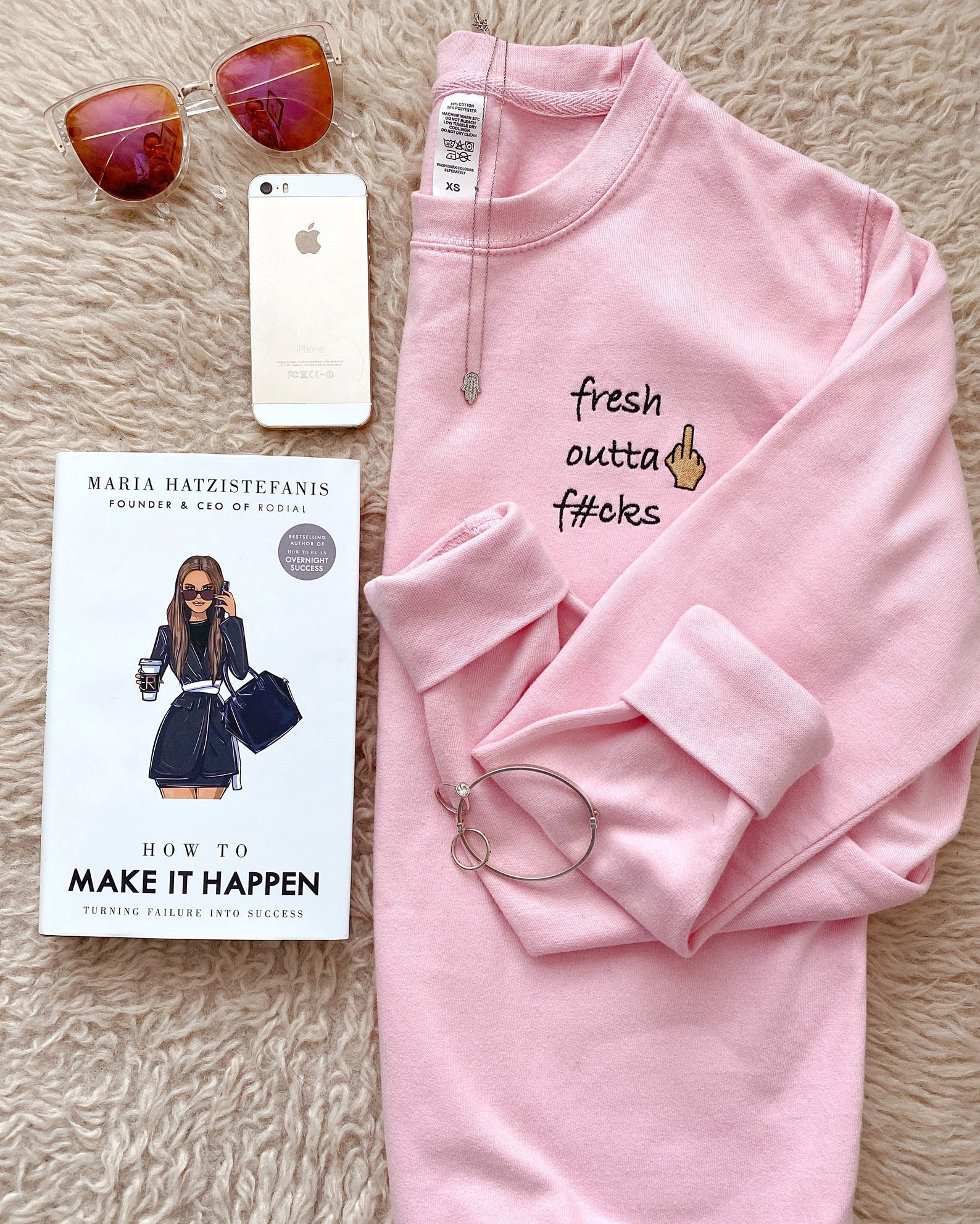 "A pink jumper lay folded, written on it is ""fresh outta fucks"". A phone and the book ""How to Make It Happen"" sits next to the jumper."