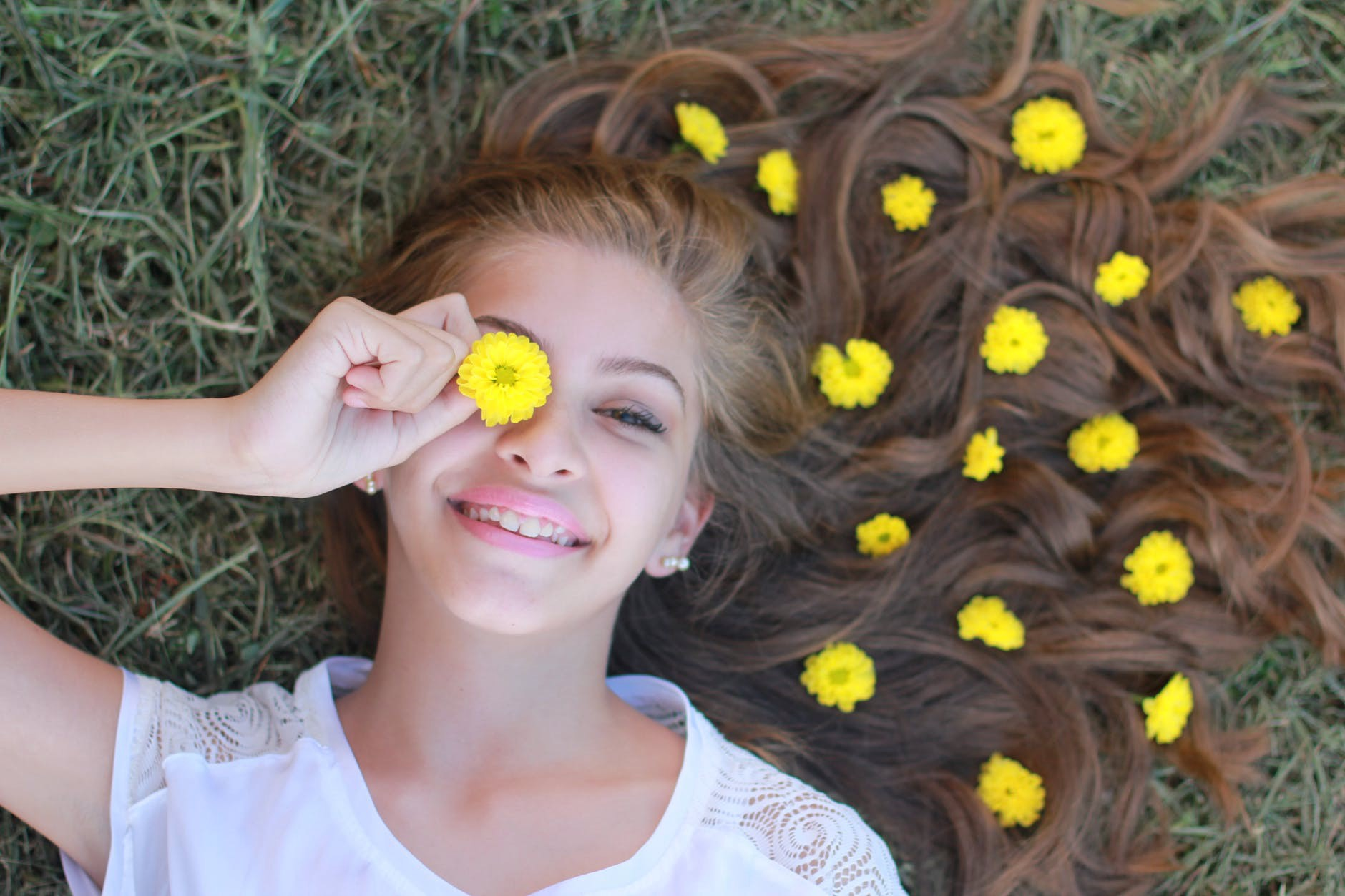Happy teen lying on a grassy field and wearing yellow flowers in her hair