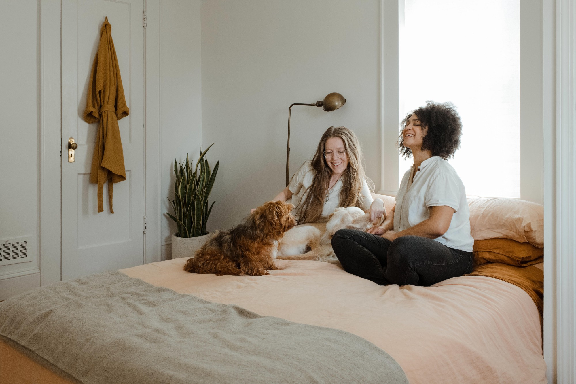 two women and a dog sitting on a bed