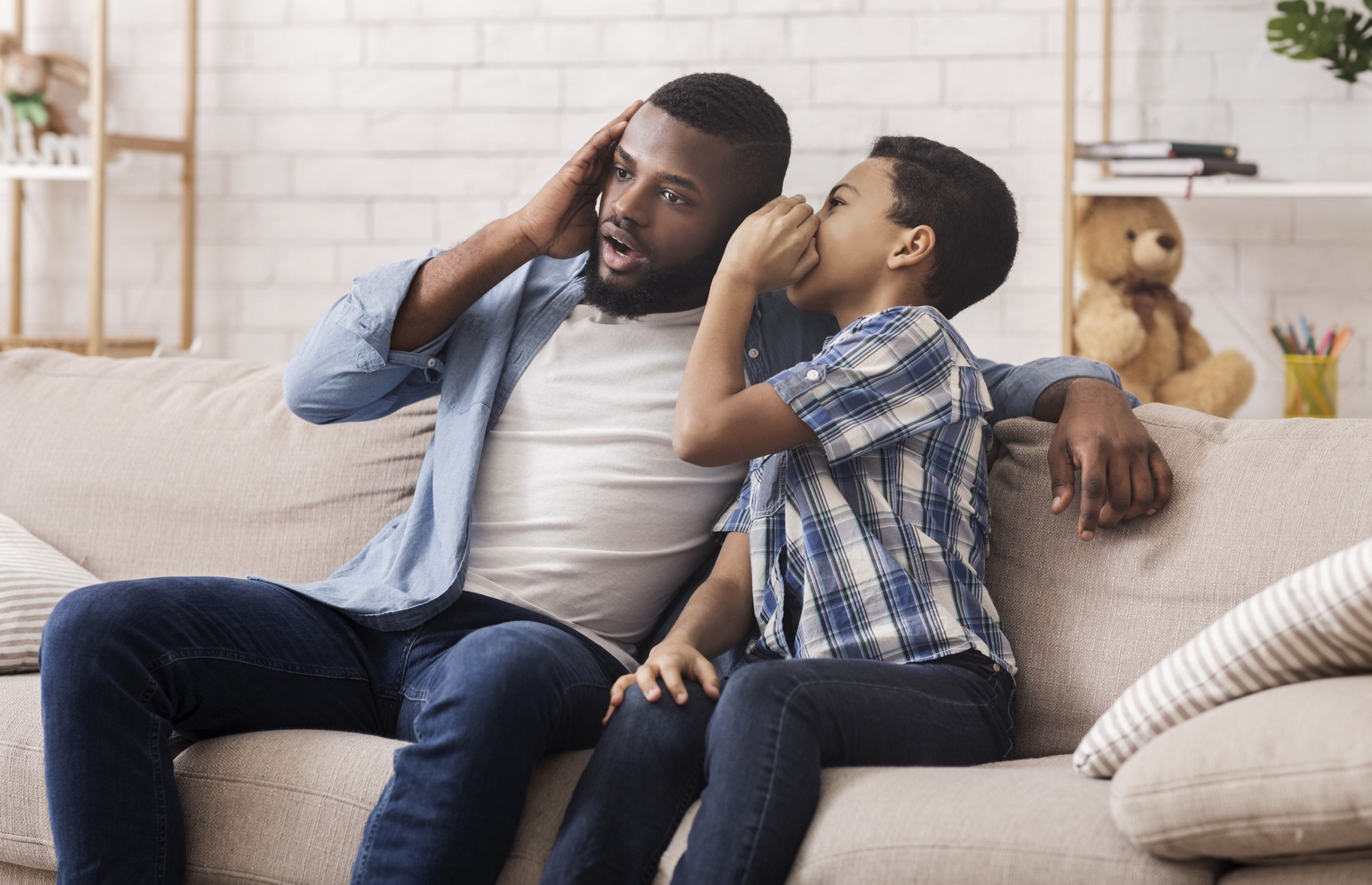 Little boy whispering into Dad's ear while sitting on couch.