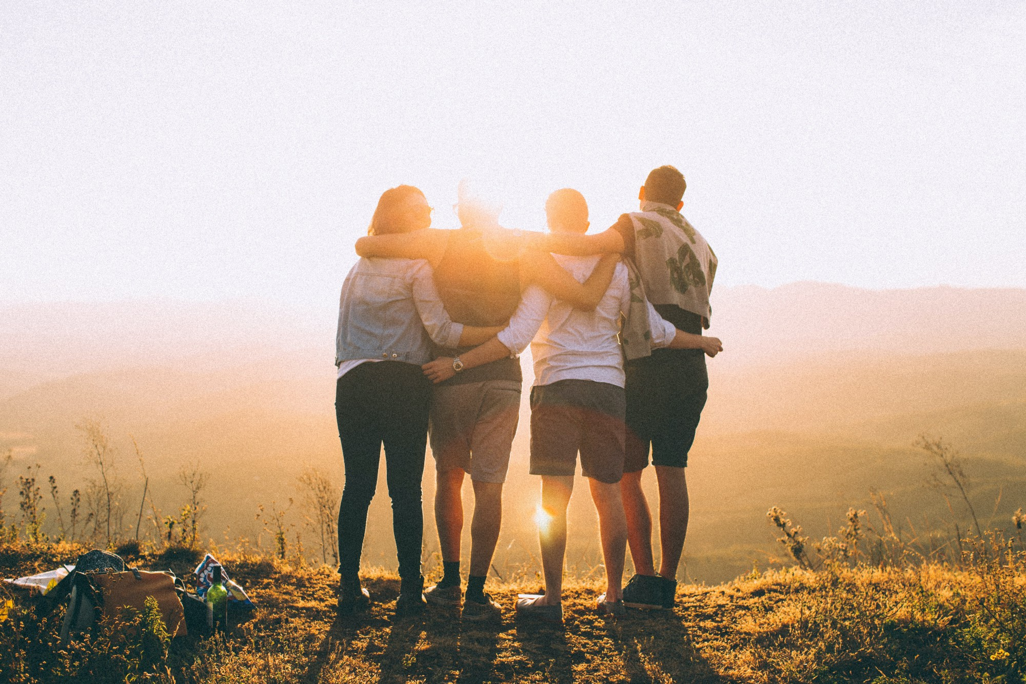 Group of friends hugging in the sunset light
