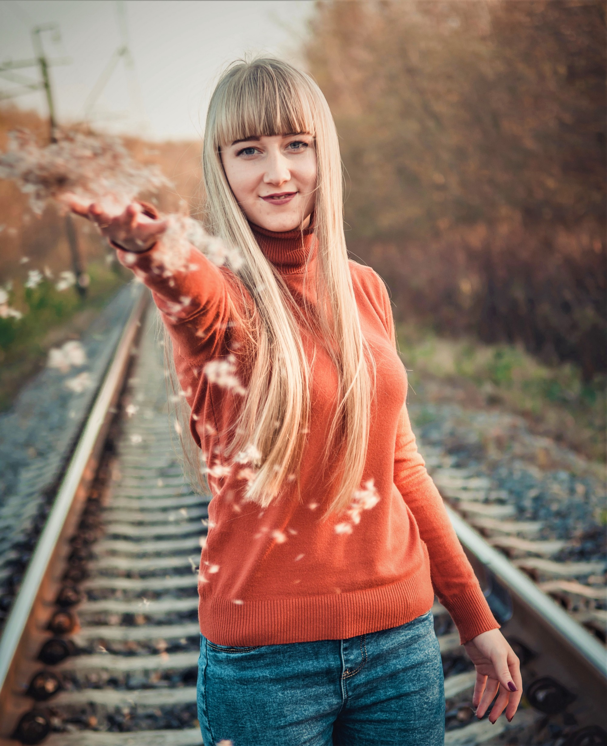 smiling girl with long blonde hair wearing long sleeve orange sweater standing on railroad tracks