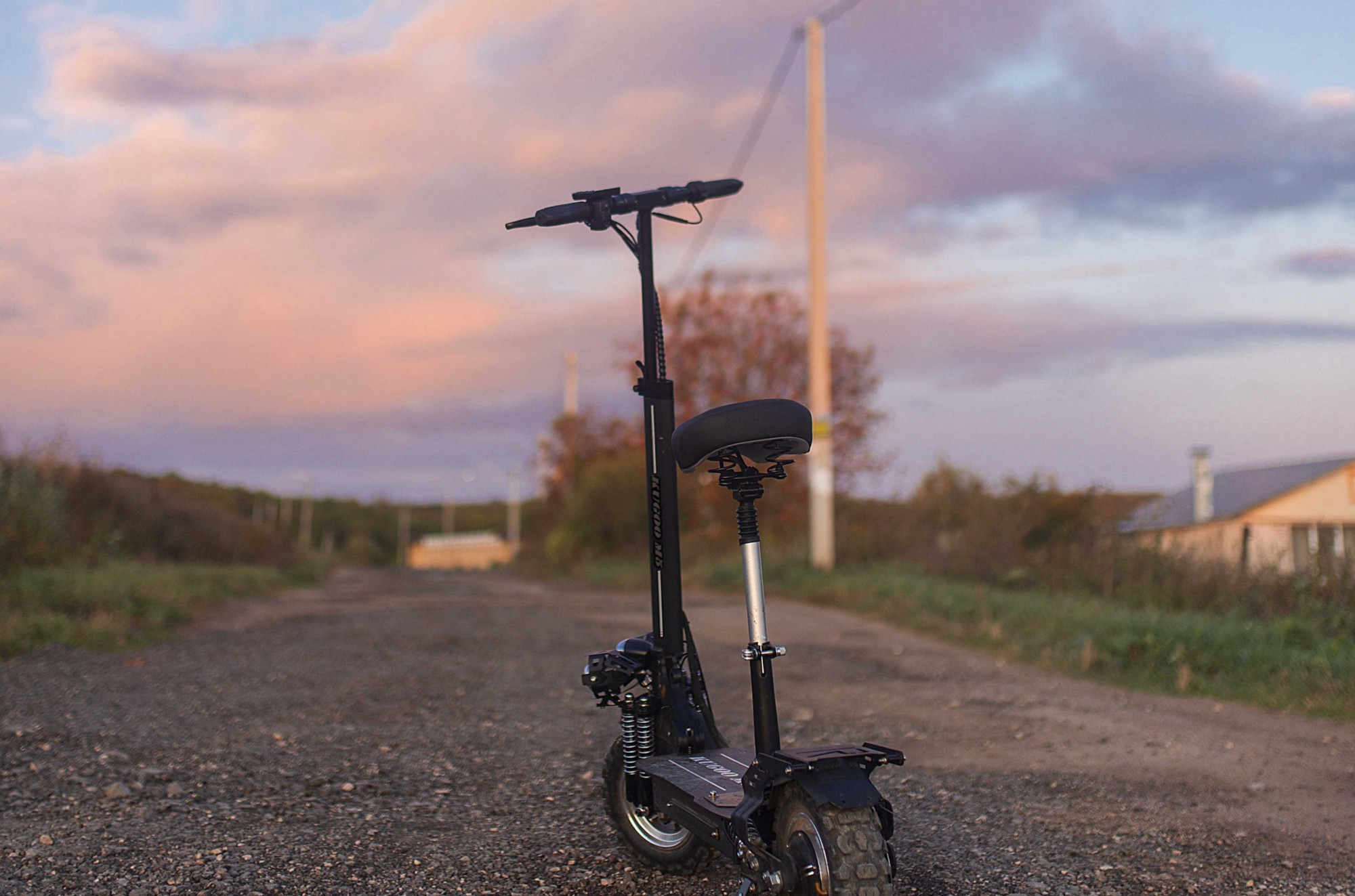 An electric scooter is parked on a country road, as the sun sets.