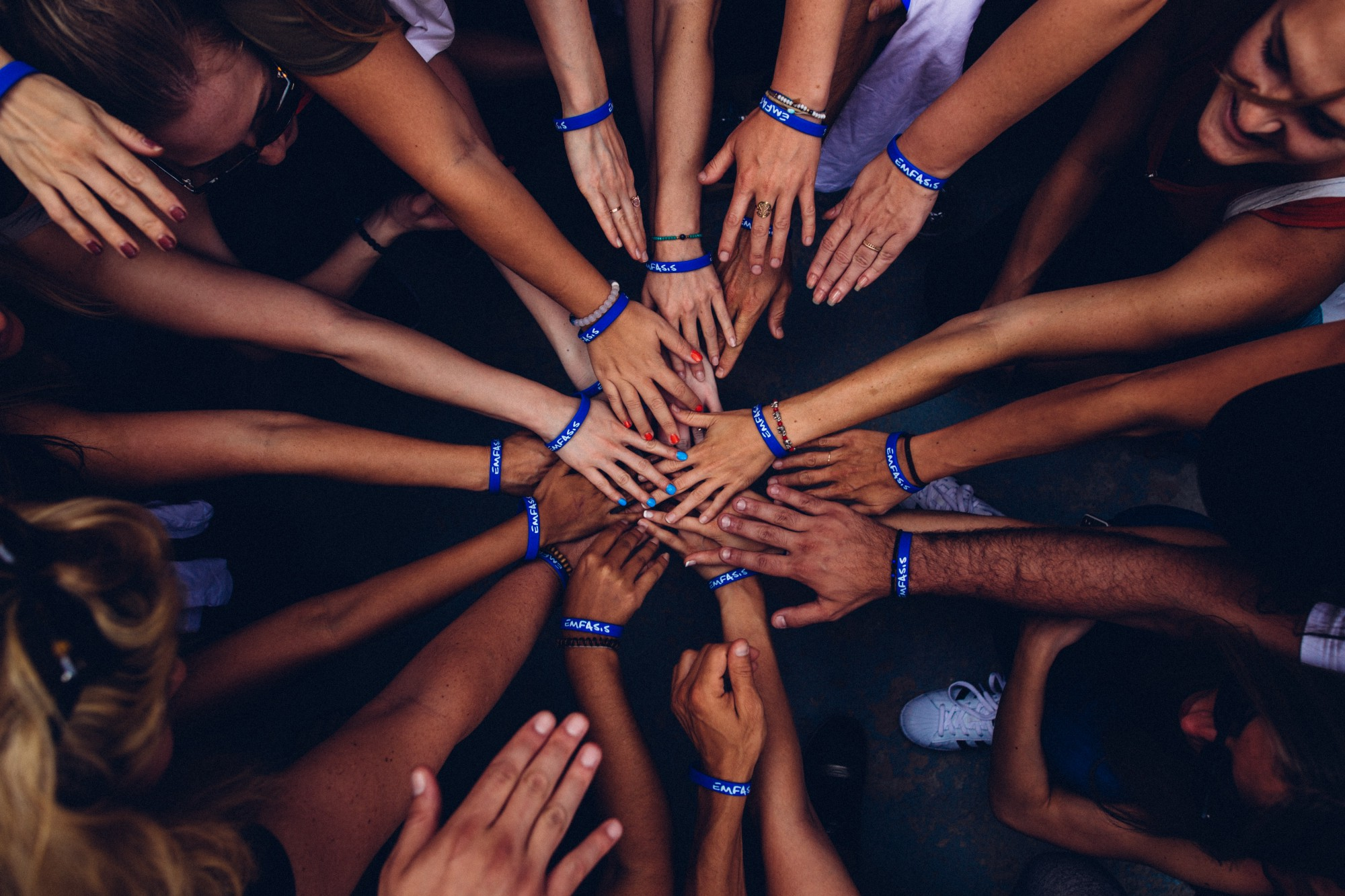 several hands placed on top of one another to show teamwork and community