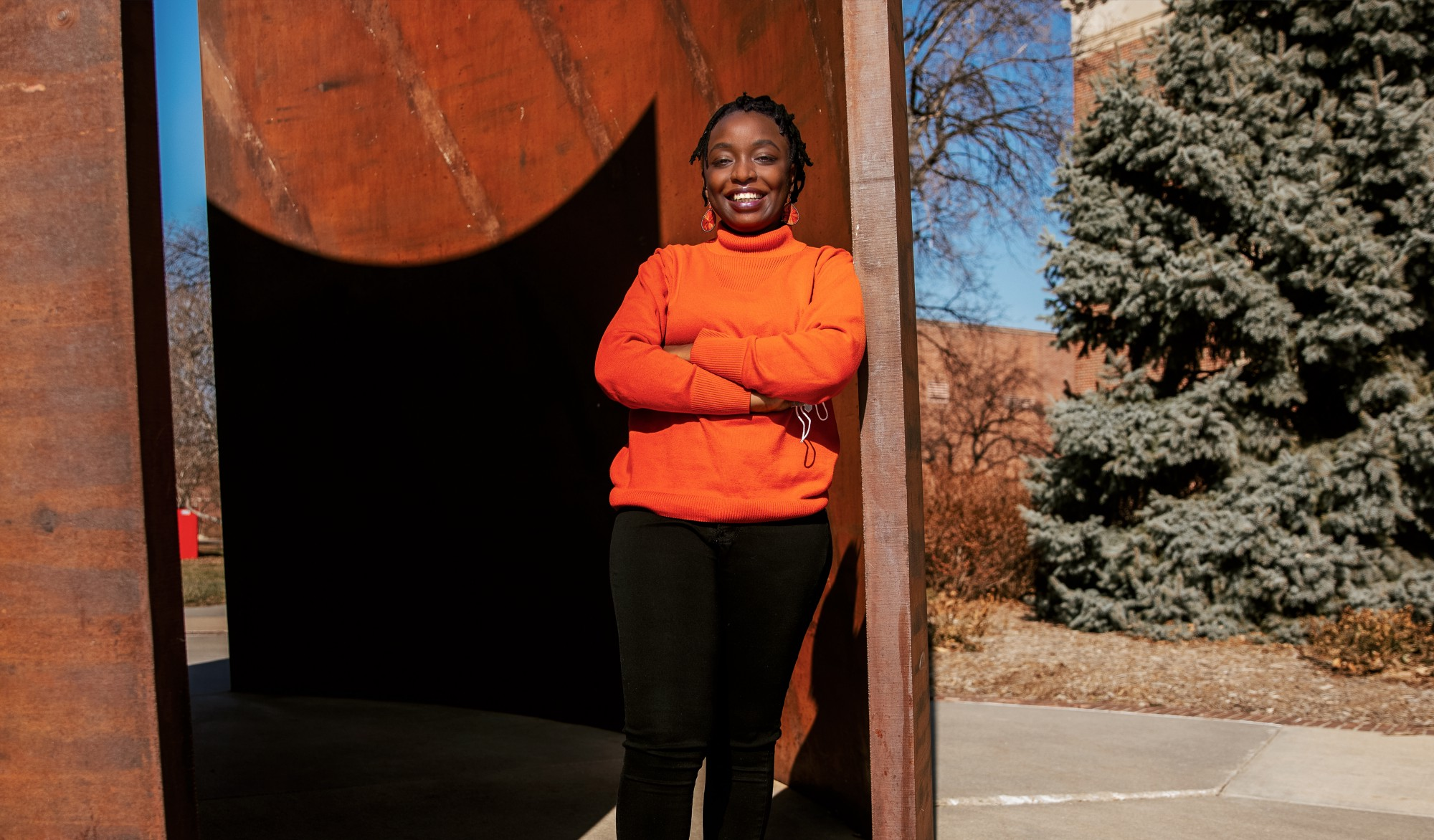 Shemsa leans against the the Greenpoint sculpture near Love Library and smiles for the camera