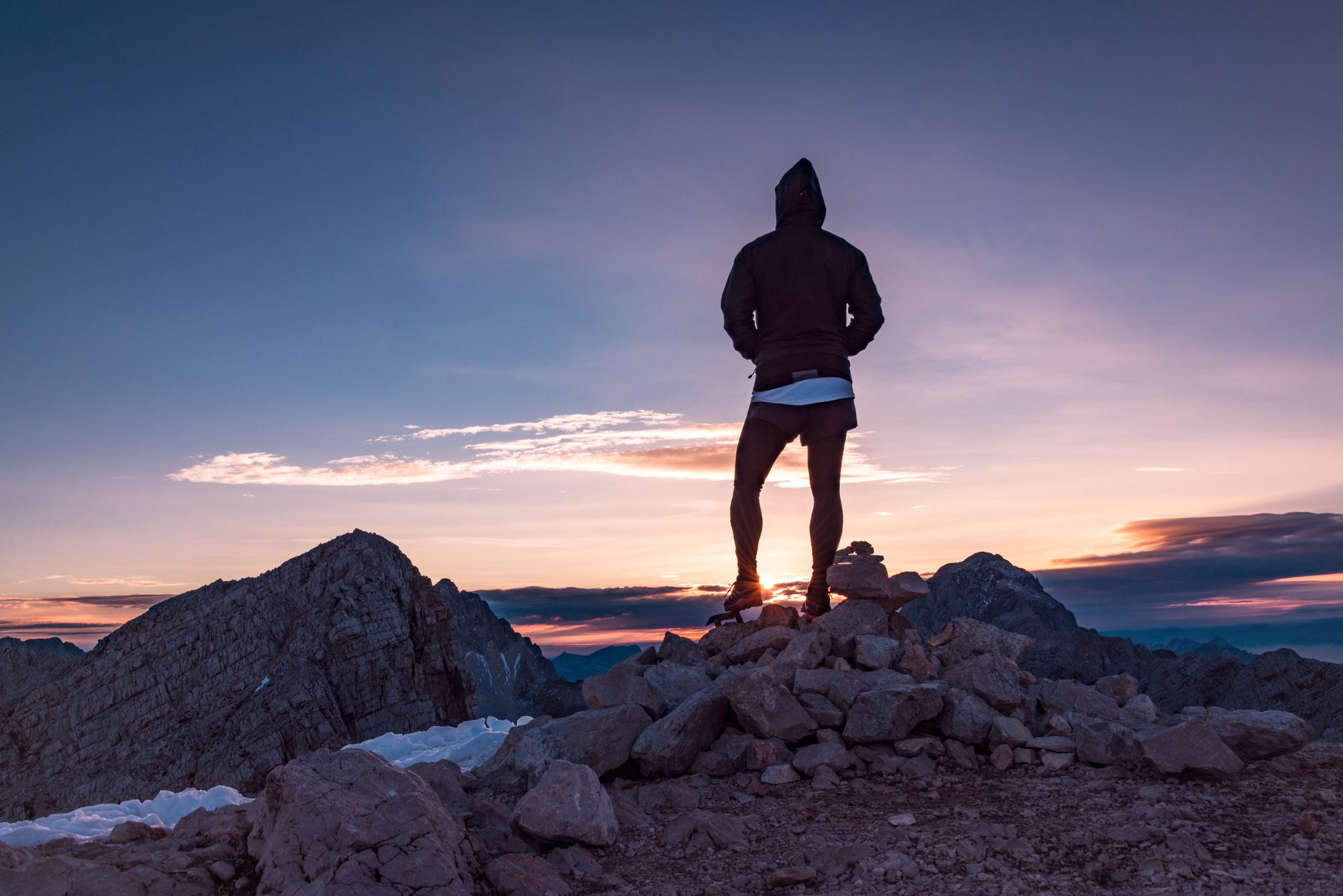 A person looking at the sunset while on a mountain.