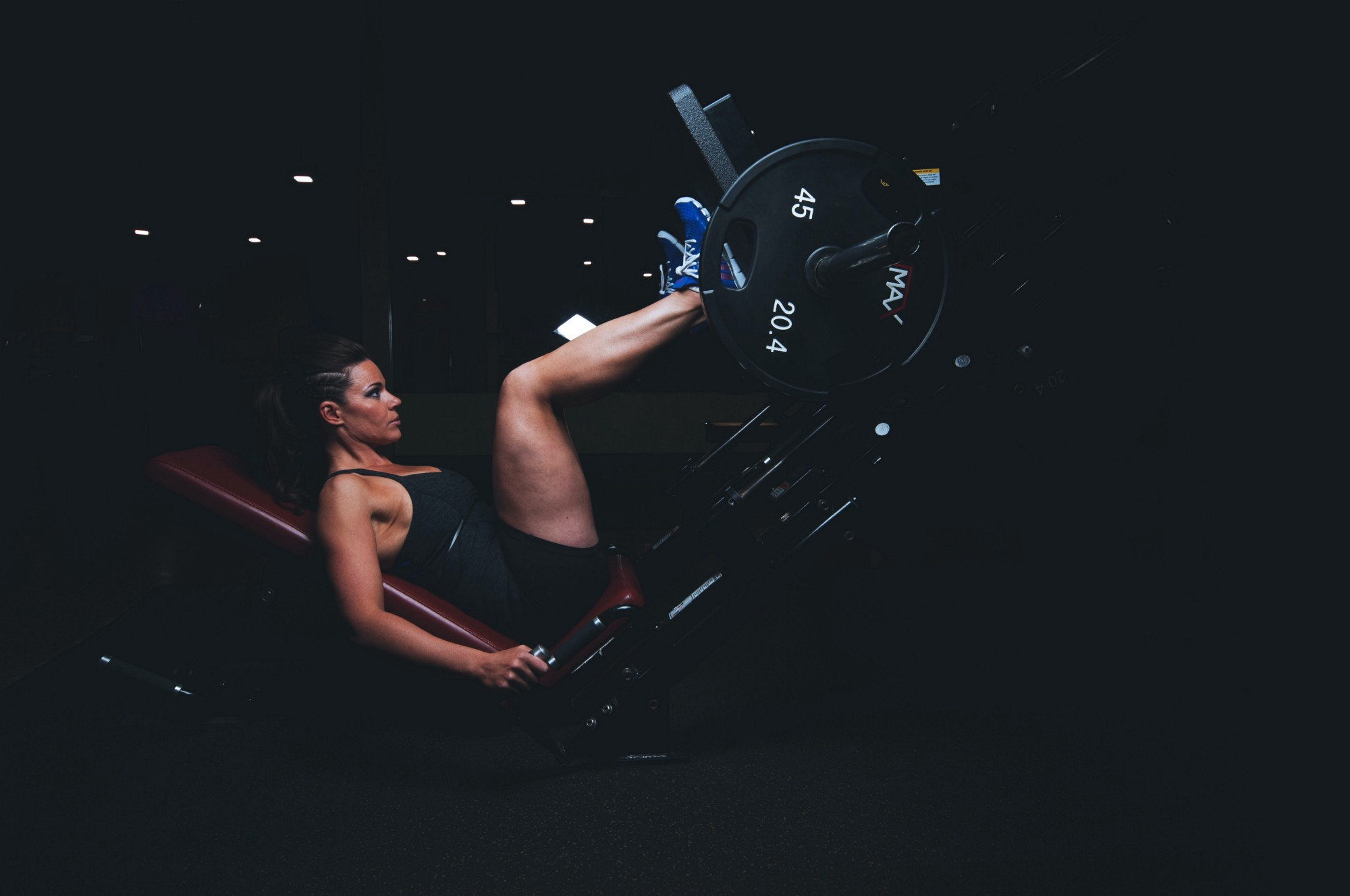 A woman against a dark background uses a leg press machine. She looks strong and focused.