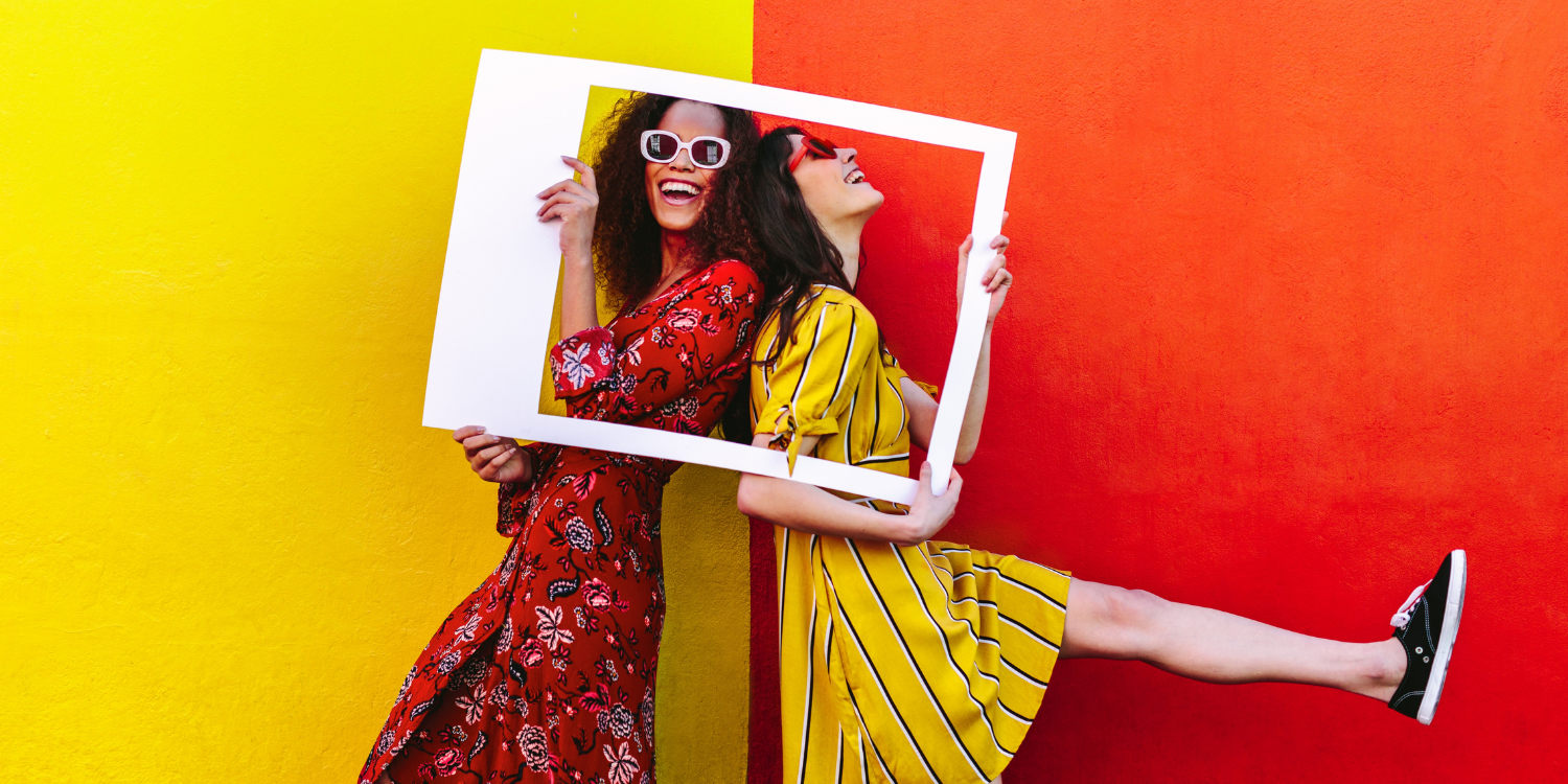 Two women standing back-to-back hold up a picture frame against a bright yellow and red background