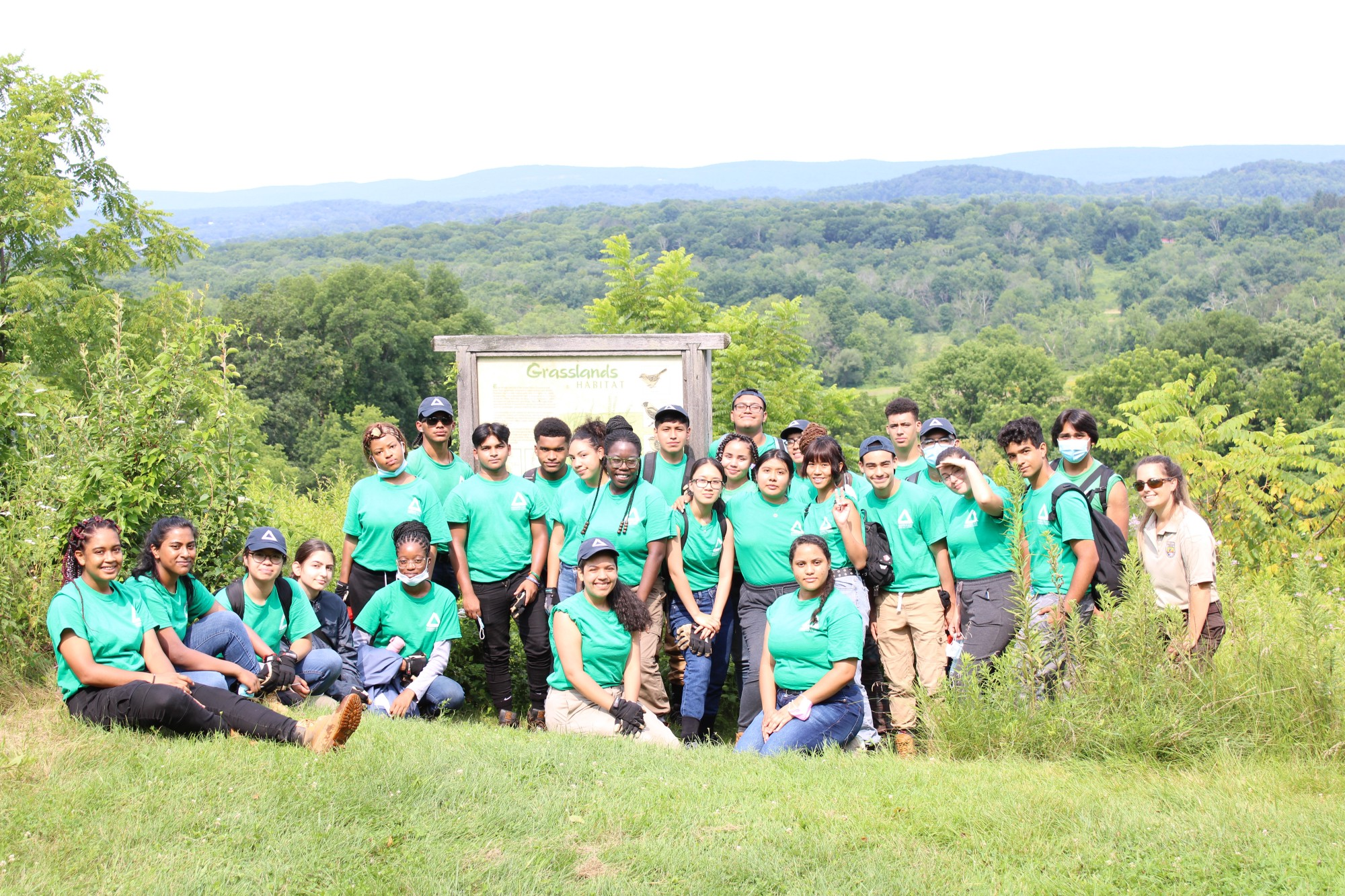 A group photo of the groundwork team wearing green shirts and standing in front a beautiful mountainous overlook