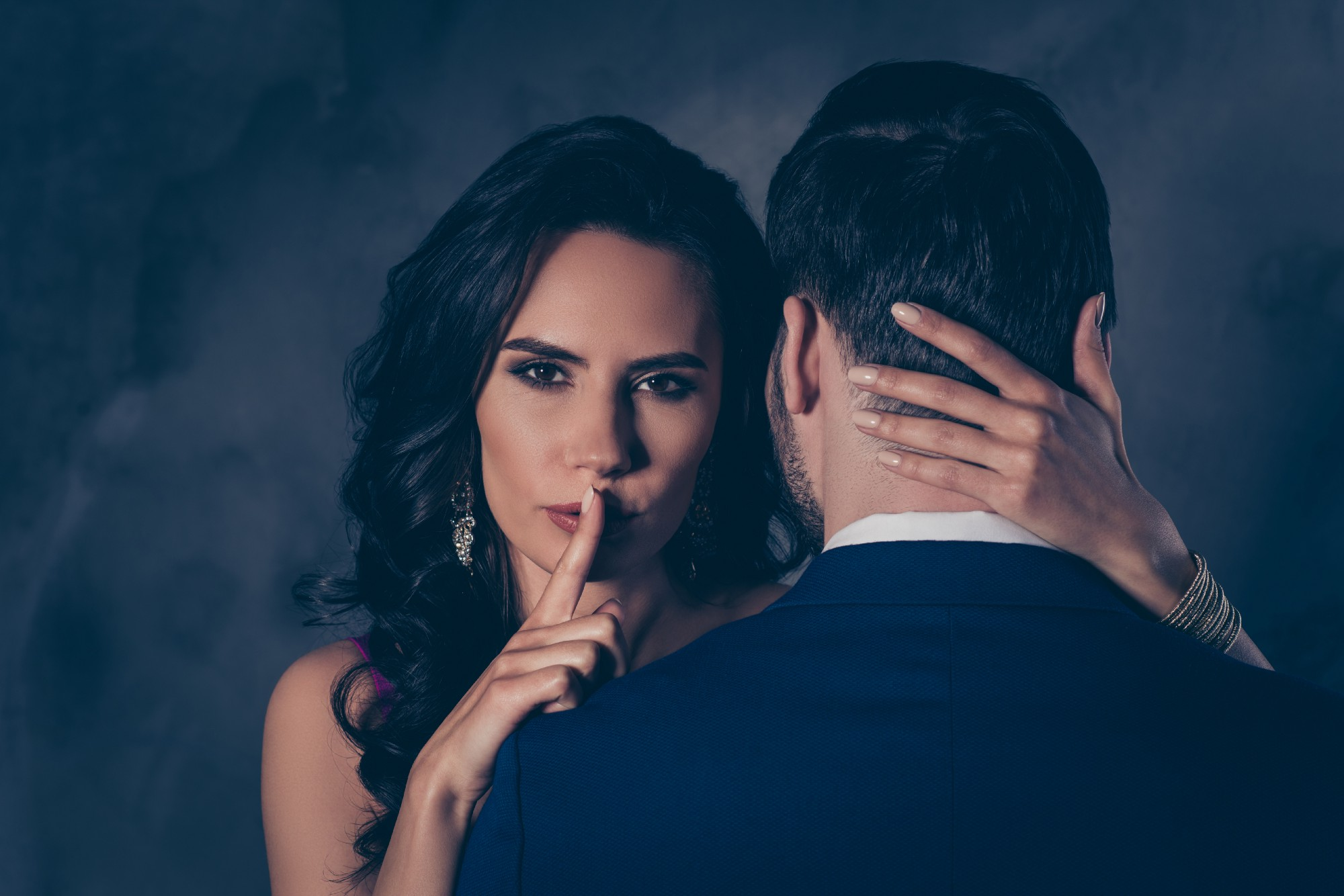 A couple. The woman is looking at the camera and holding her finger to her lips.