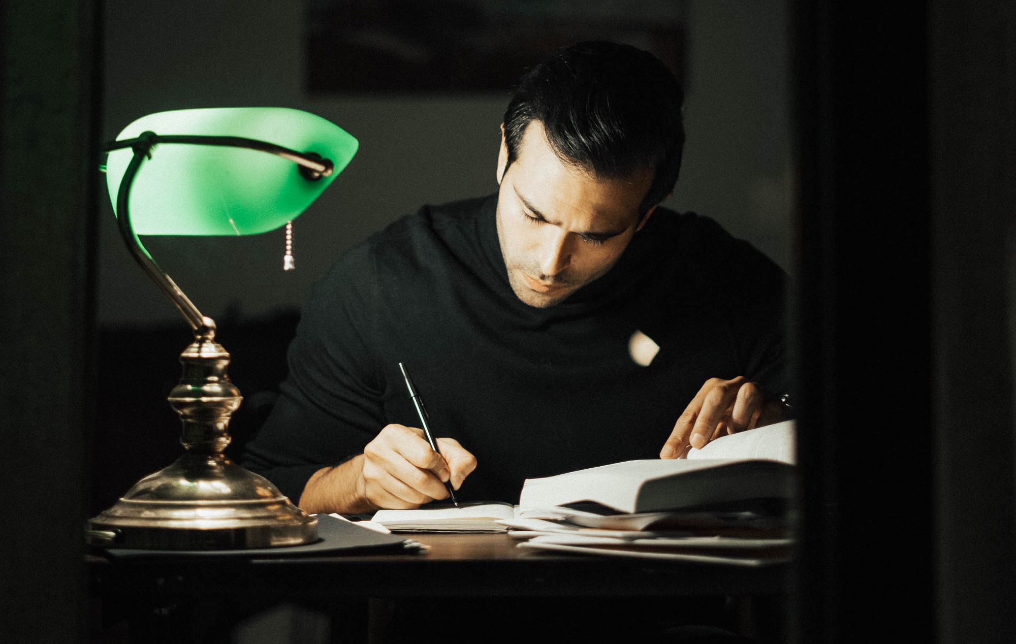 Handsome man writing on a desk