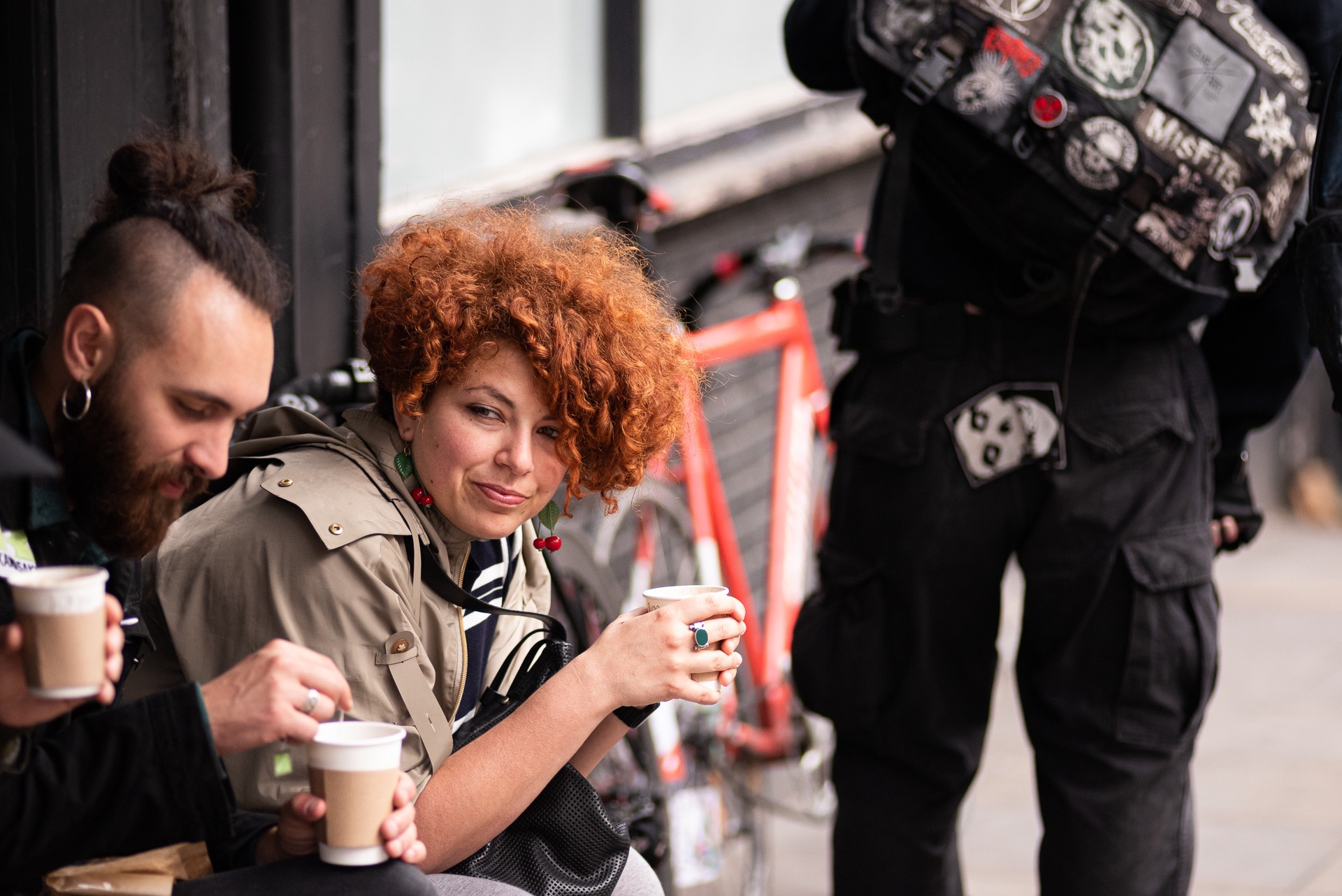 A woman with red curly hair looks on with a cup of coffee.