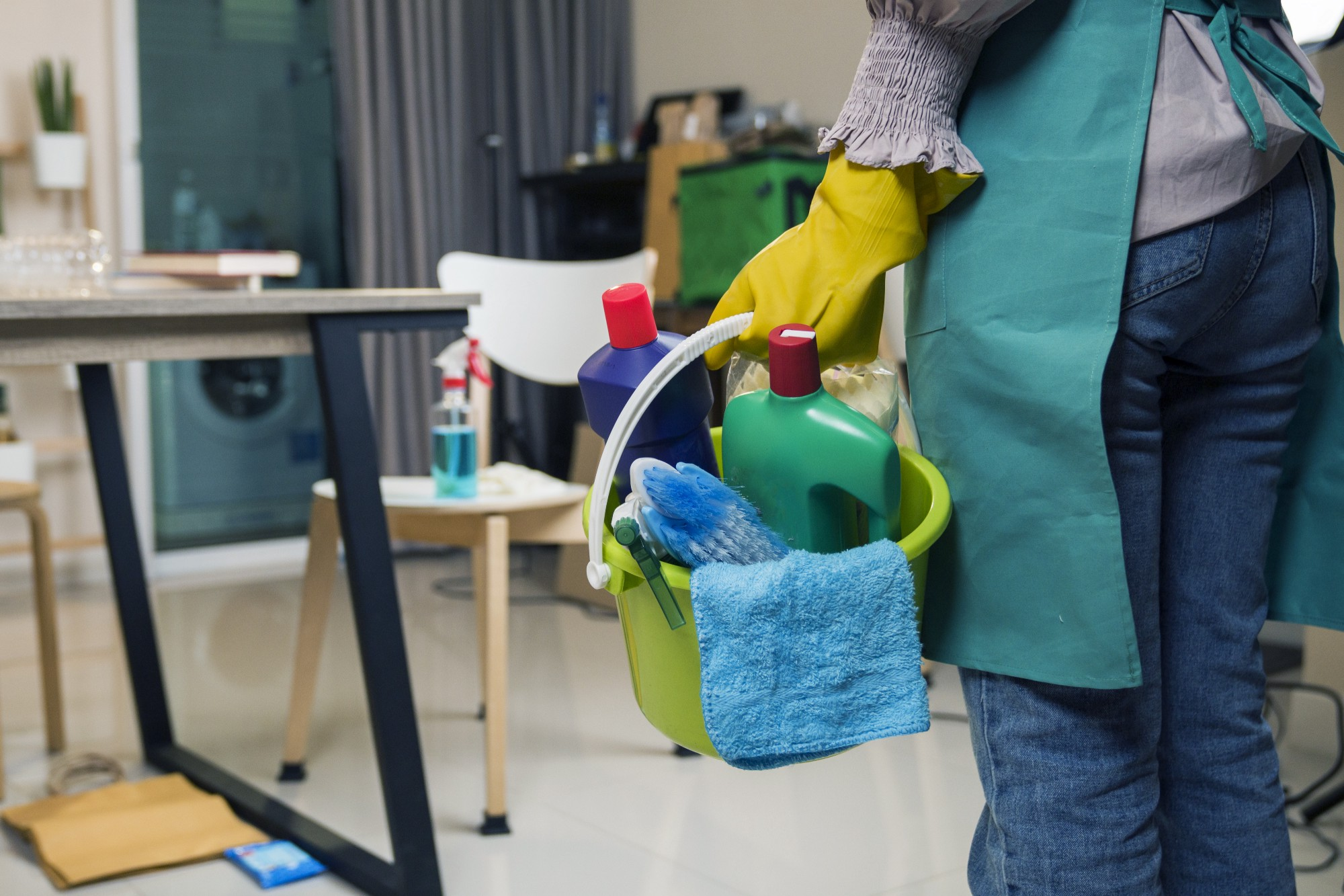 A waist-down shot of a maid, seen from behind, holding a bucket of cleaning products in a small room.