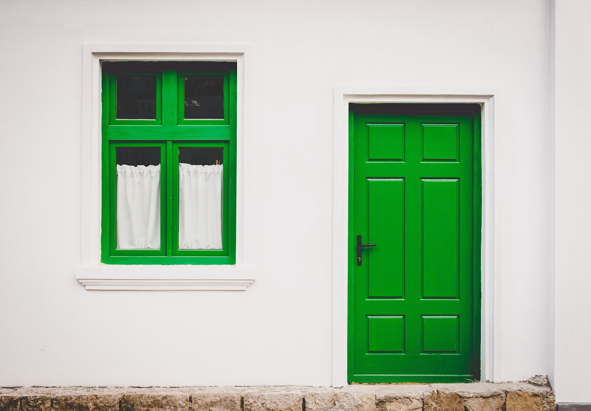 A green window and door on a clean white wall