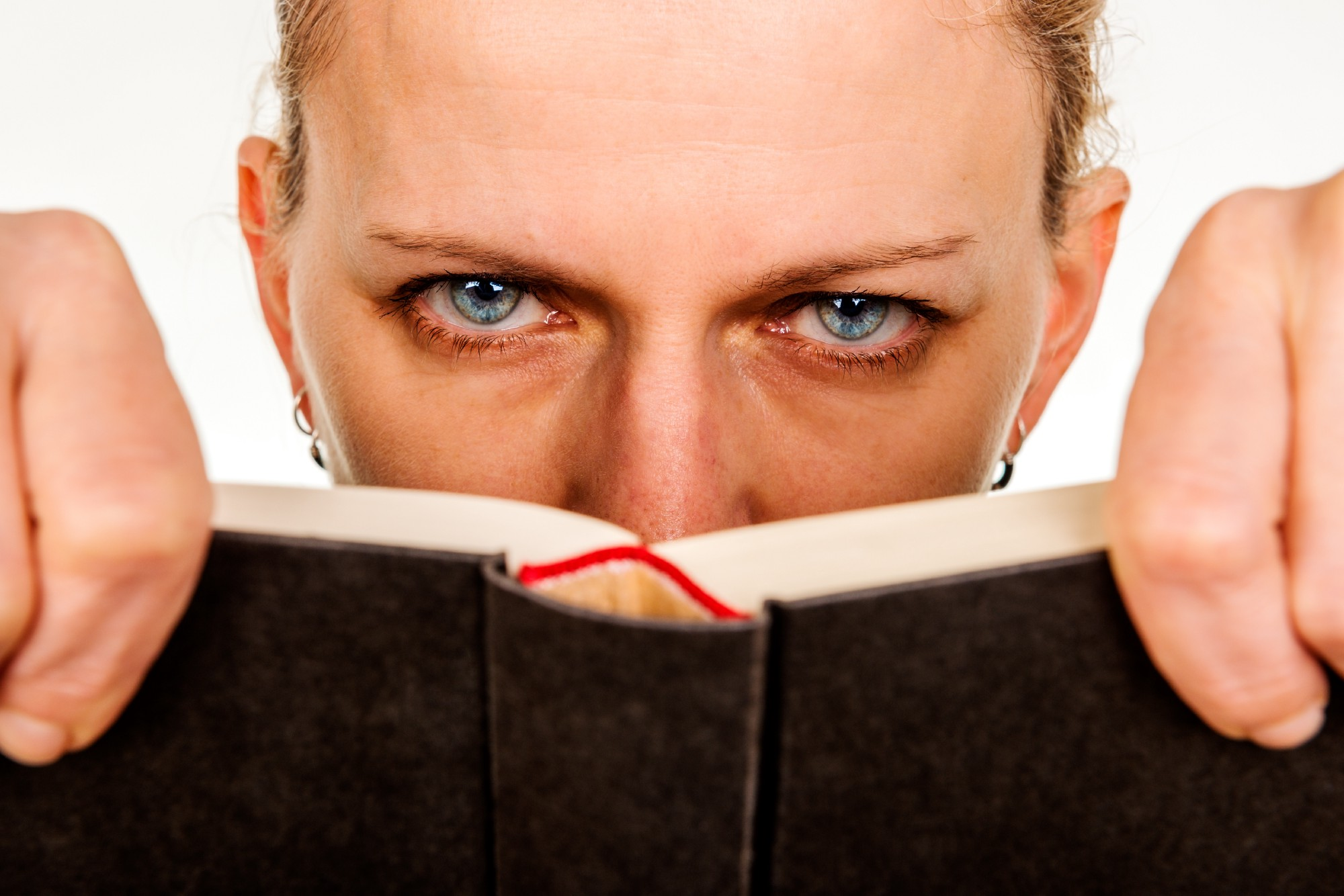 A woman looks directly at us over the top of a book she has been reading. It is clear she is unhappy with what she has just read.