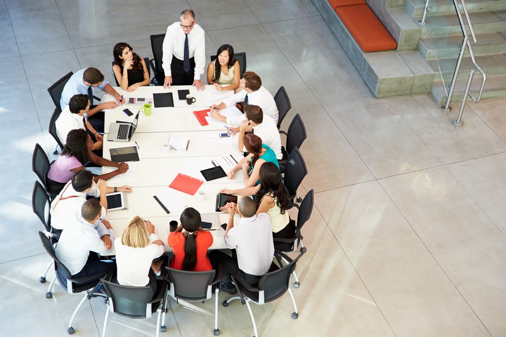 Image of a table with employees working (one is standing at the head of the table)