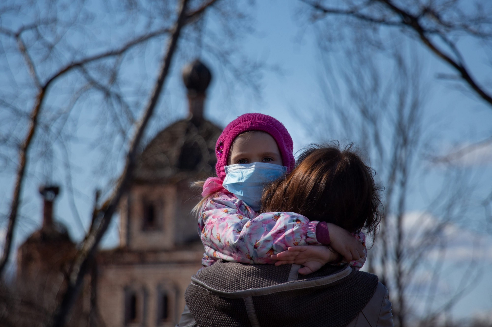 Child being held by a woman in the fall. Child is wearing a mask.
