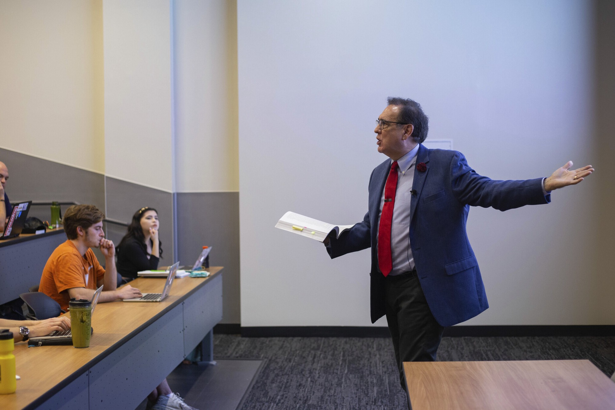 Thomas Garza stands in the front of a classroom of students holding a book and gesturing to the screen behind him.