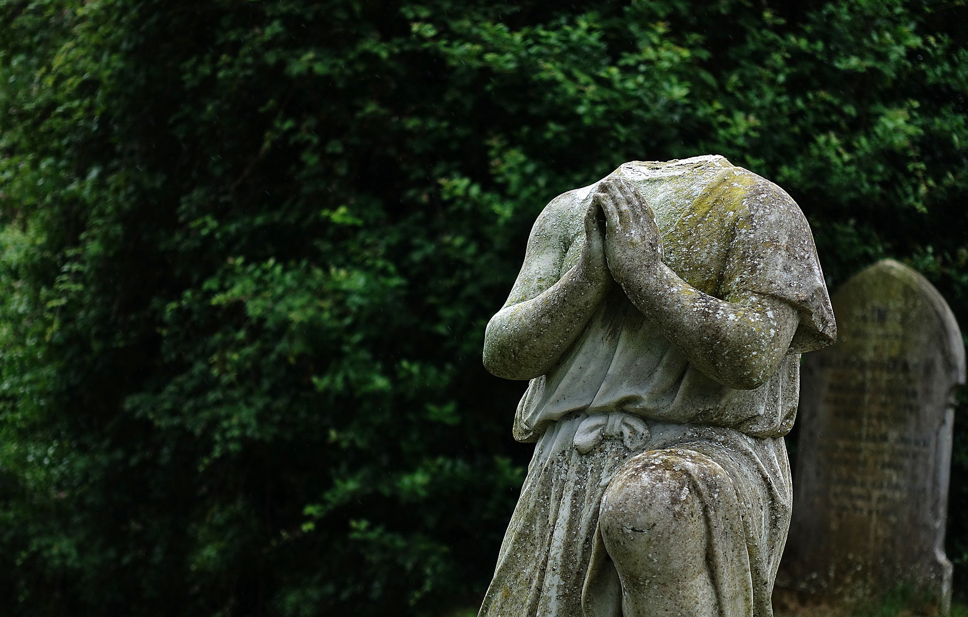 A cement statue of a headless figure with hands in prayer position in a cemetary
