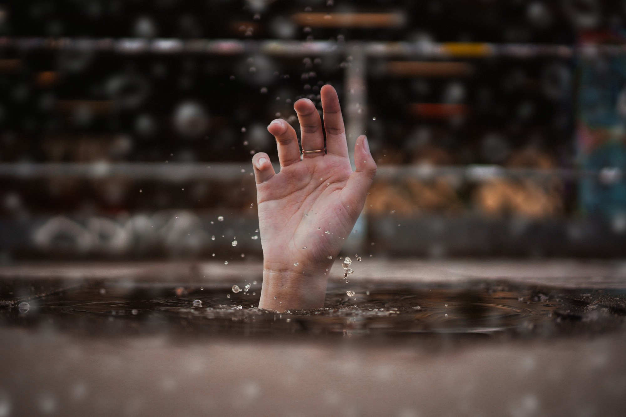 Hand thrusting through water from drowning victim.