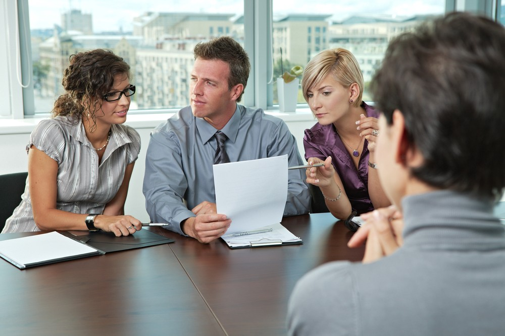 Image of three employees interviewing a candidate