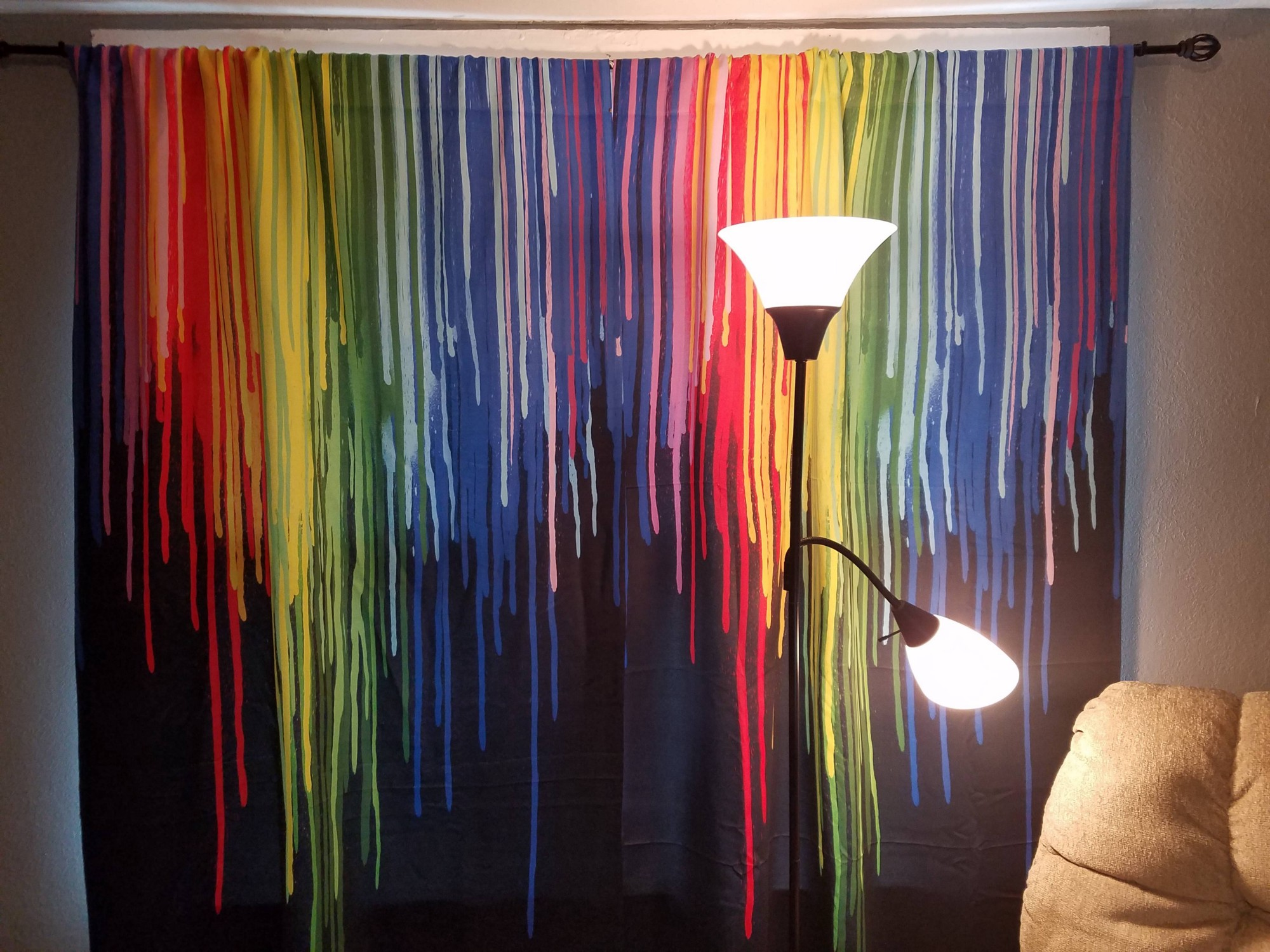 Black Curtains with rainbow colored paint effect. In front of the curtains, a light and an easy chair