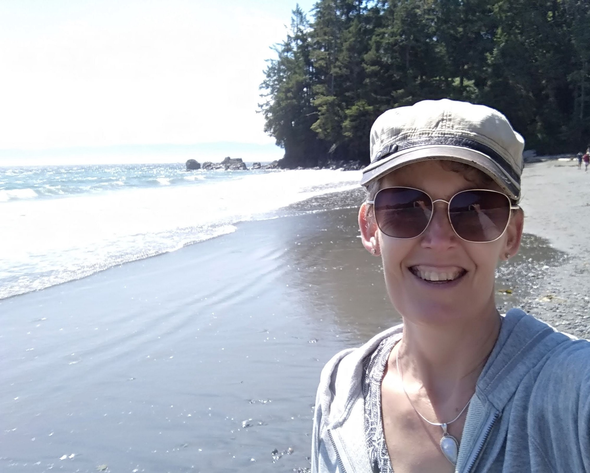 Photo of author, Gill McCulloch standing on a sandy beach in Sooke, BC, Canada. The sun is shining on waves with trees in the background.