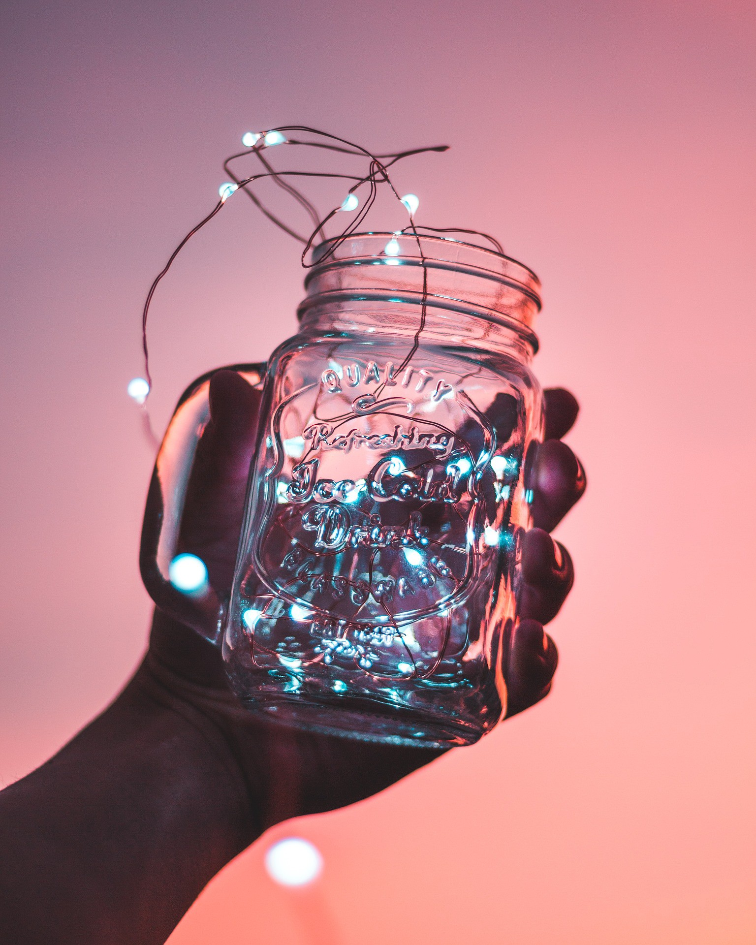 hand holding a mason jar with twinkle lights