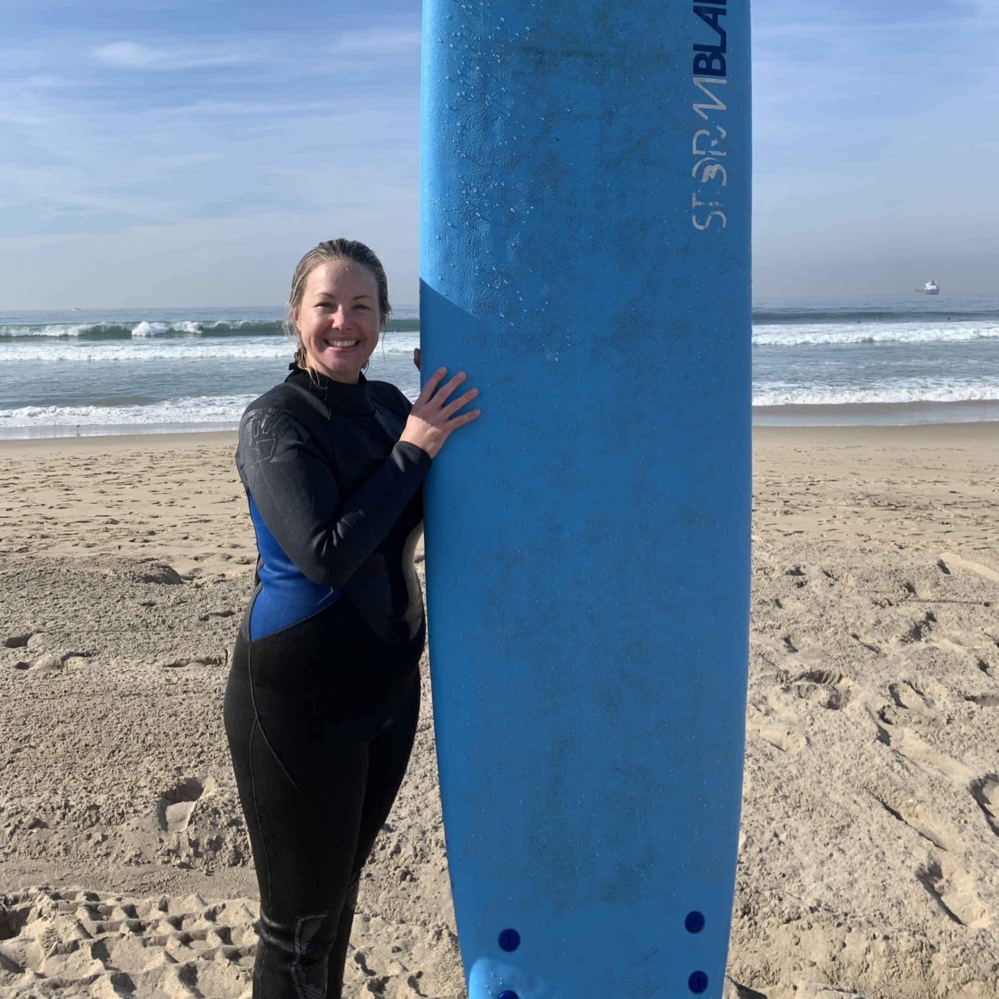 Jeanie stands on the beach in a wet suit, holding a surf board.