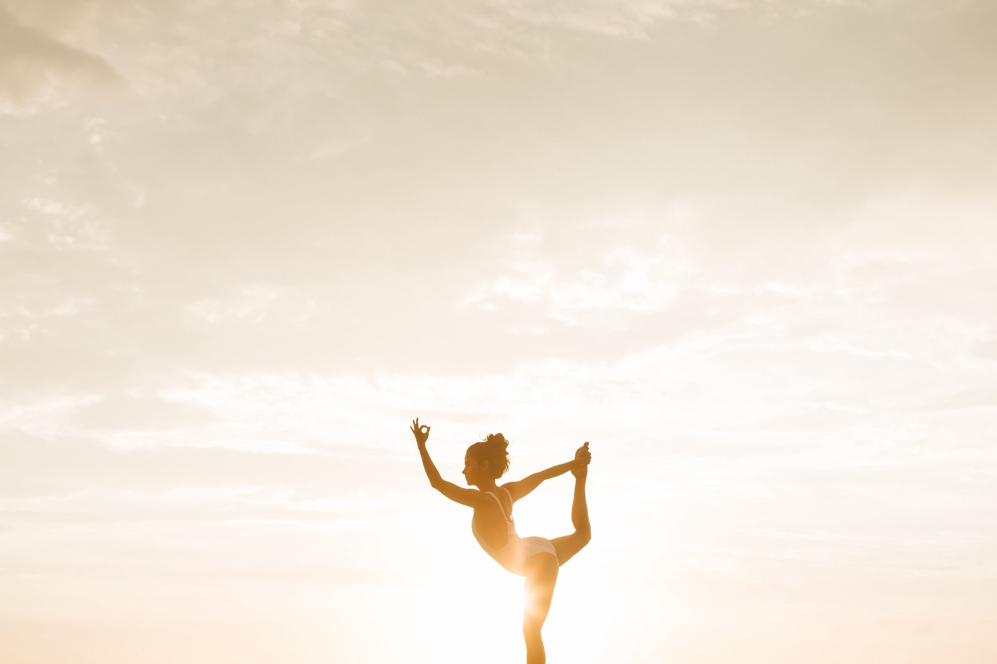 woman doing a yoga with sun shining behind her