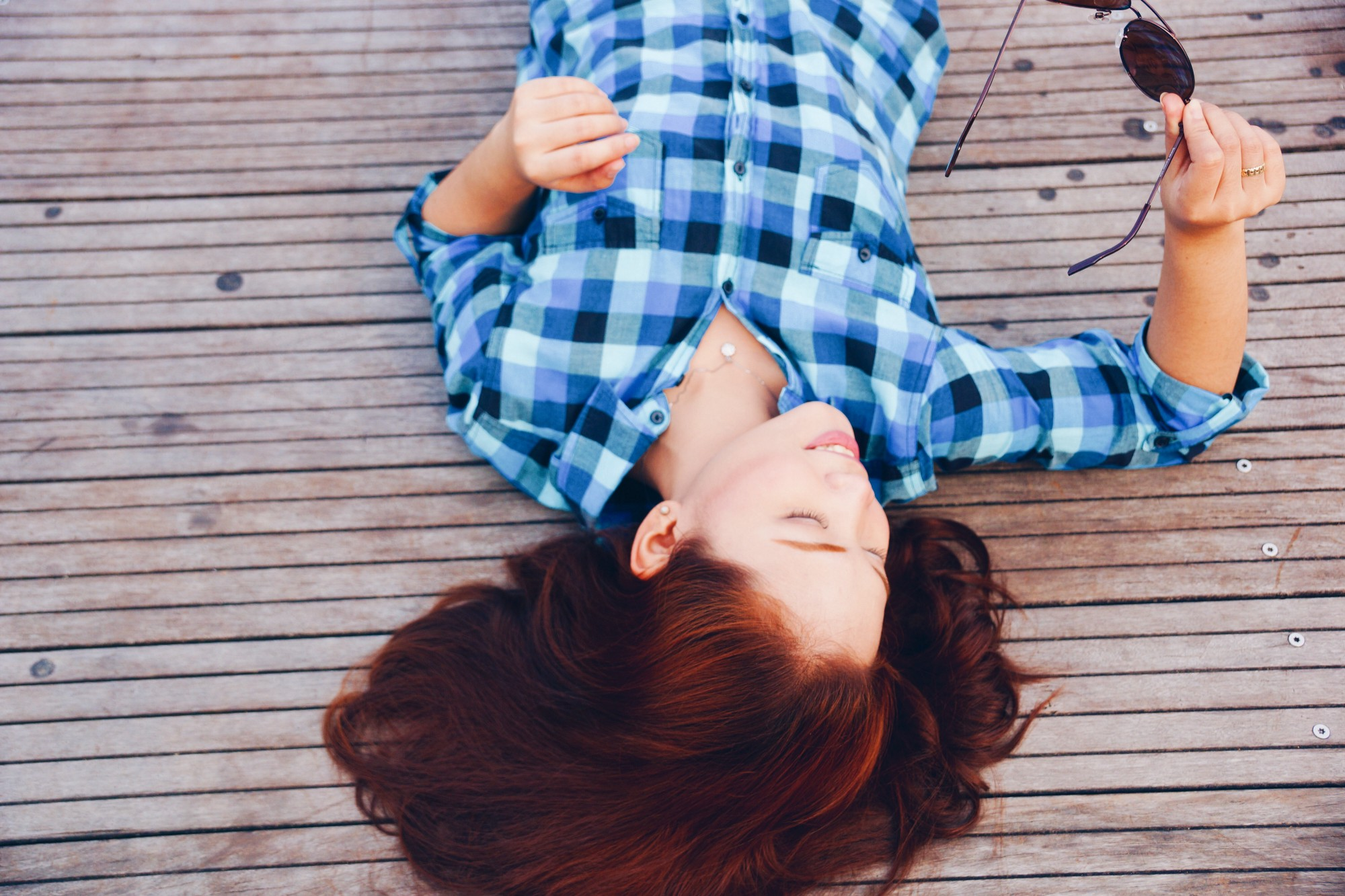 girl with long dark hair wearing blue plaid shirt holding sunglasses laying on wooden deck
