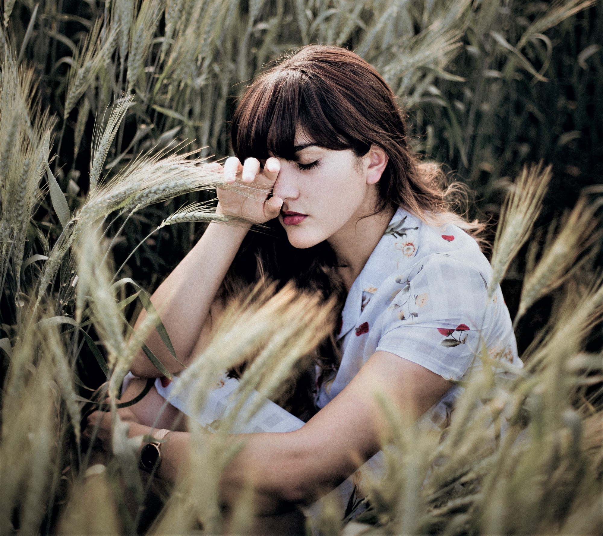 thoughtful girl with brown hair holding hand to her face sitting in field of wheat