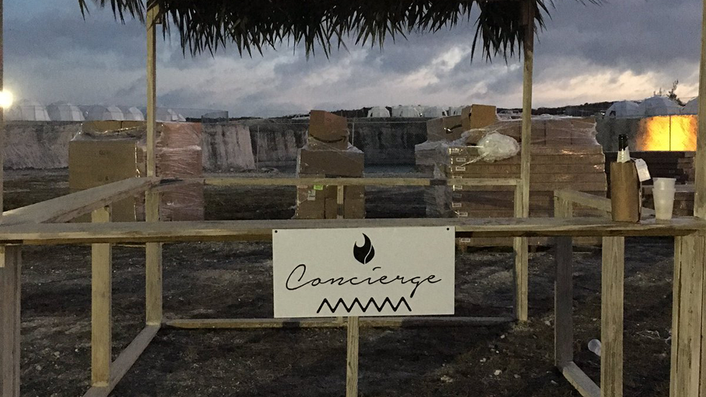 An image of the concierge stand at the festival, with boxes of building materials surrounding it