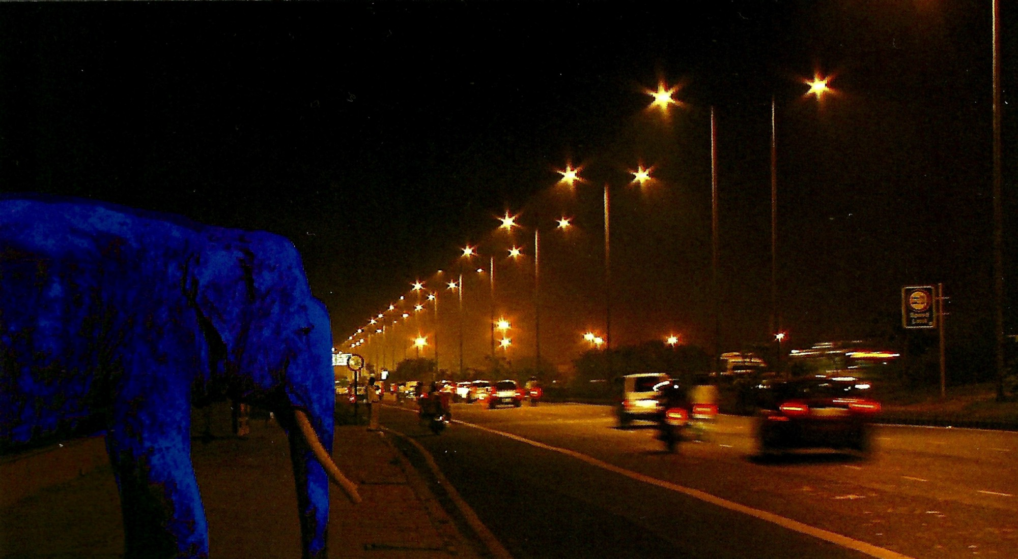 An ultramarine elephant watches cars go by on a busy highway at night, bathed in orange light