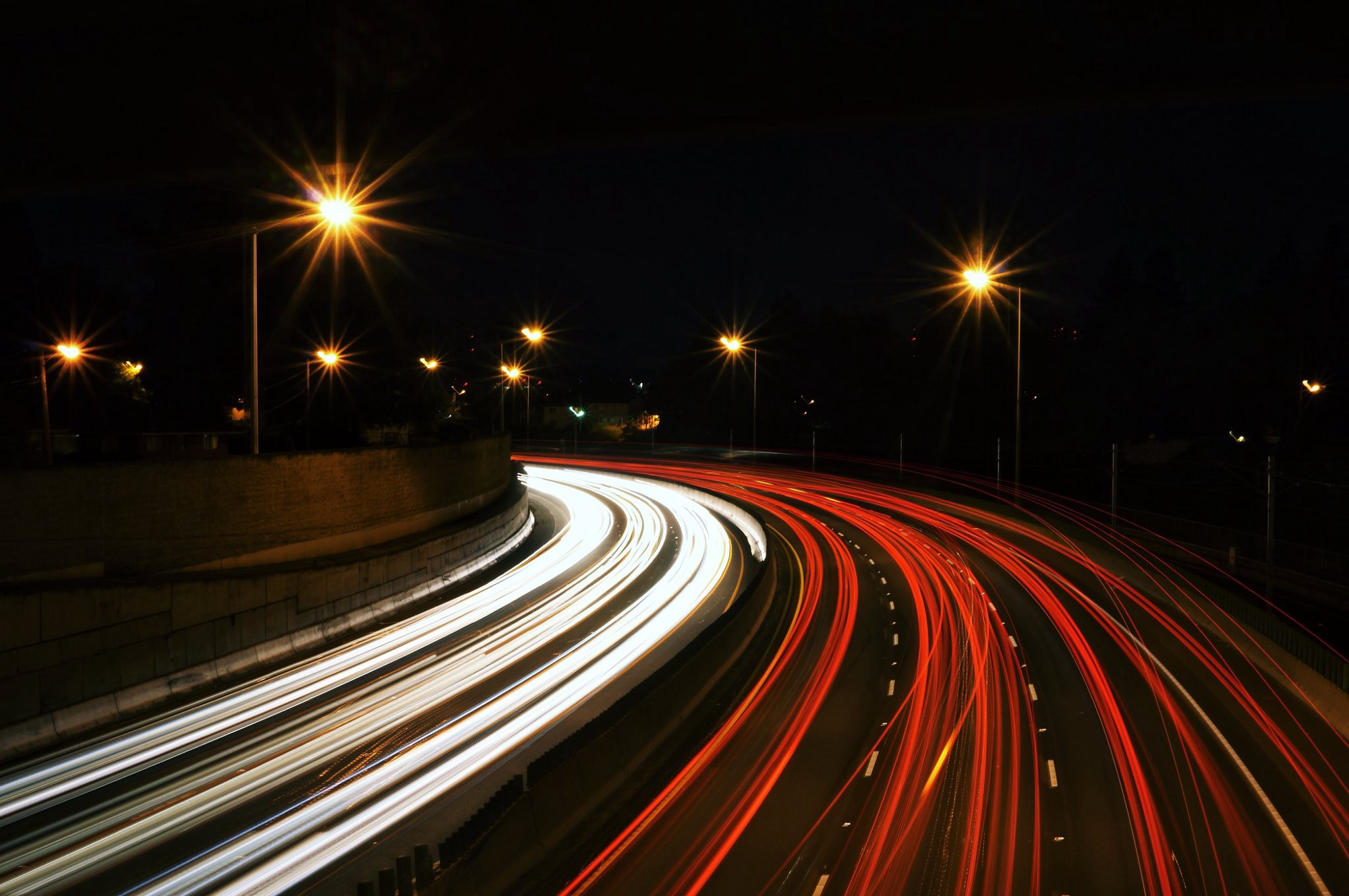 Long exposure image of a highway at night featuring red and white streaks of headlights merging into single rays of light above street lamps set against the night sky.