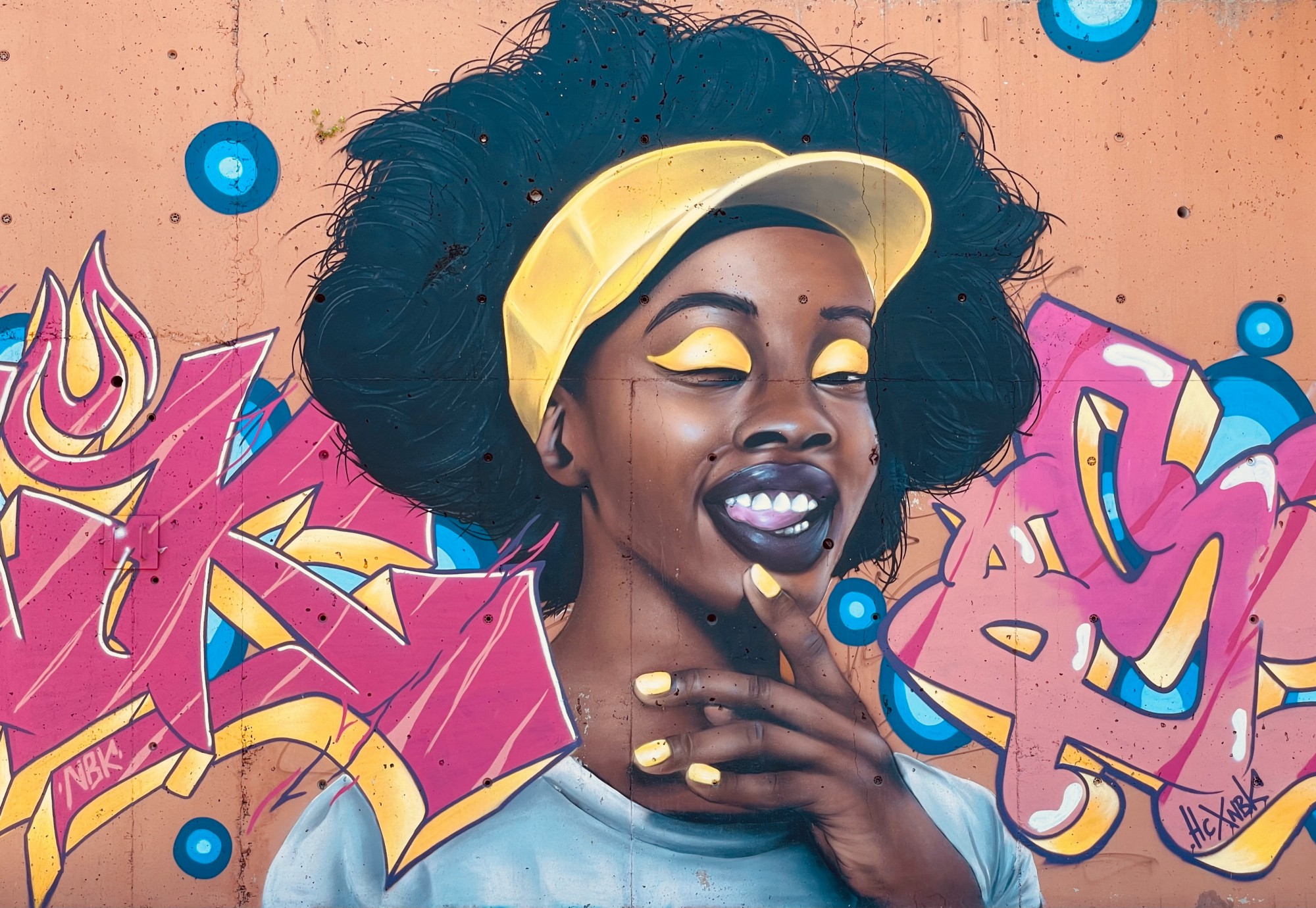 An artwork of a black lady with a yellow cap and thick black hair.
