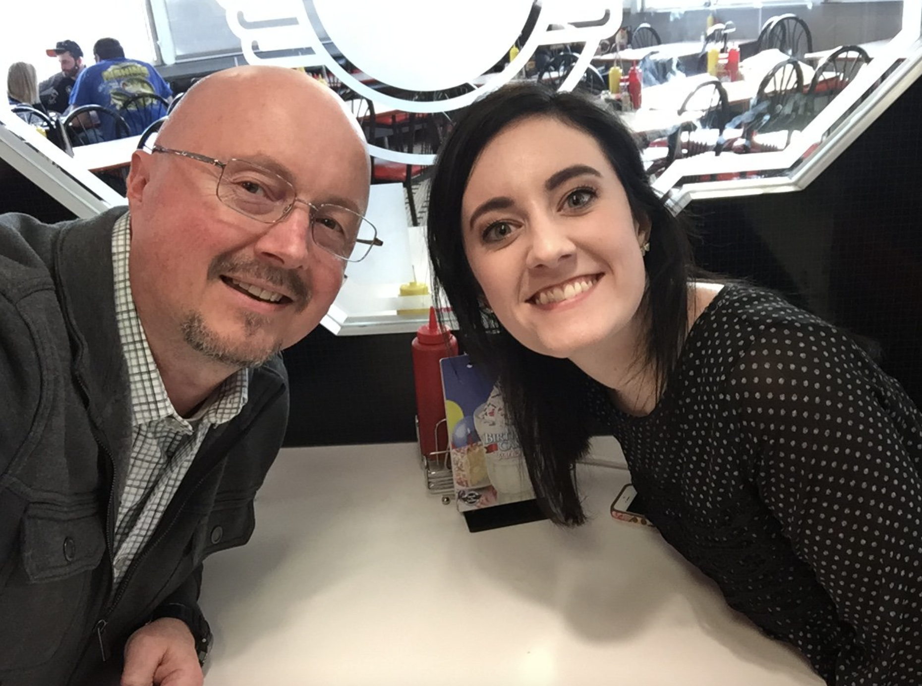 A father is a bald man with glasses, mustache and goatee, dressed in green-checkered white button-down shirt with a gray cotton button-up cardigan. His daughter is sitting across the restaurant table from him. She has medium-length black hair and she's in a black dress with white spots. They are both looking at the camera. The table is empty and they are waiting on their food and drinks.