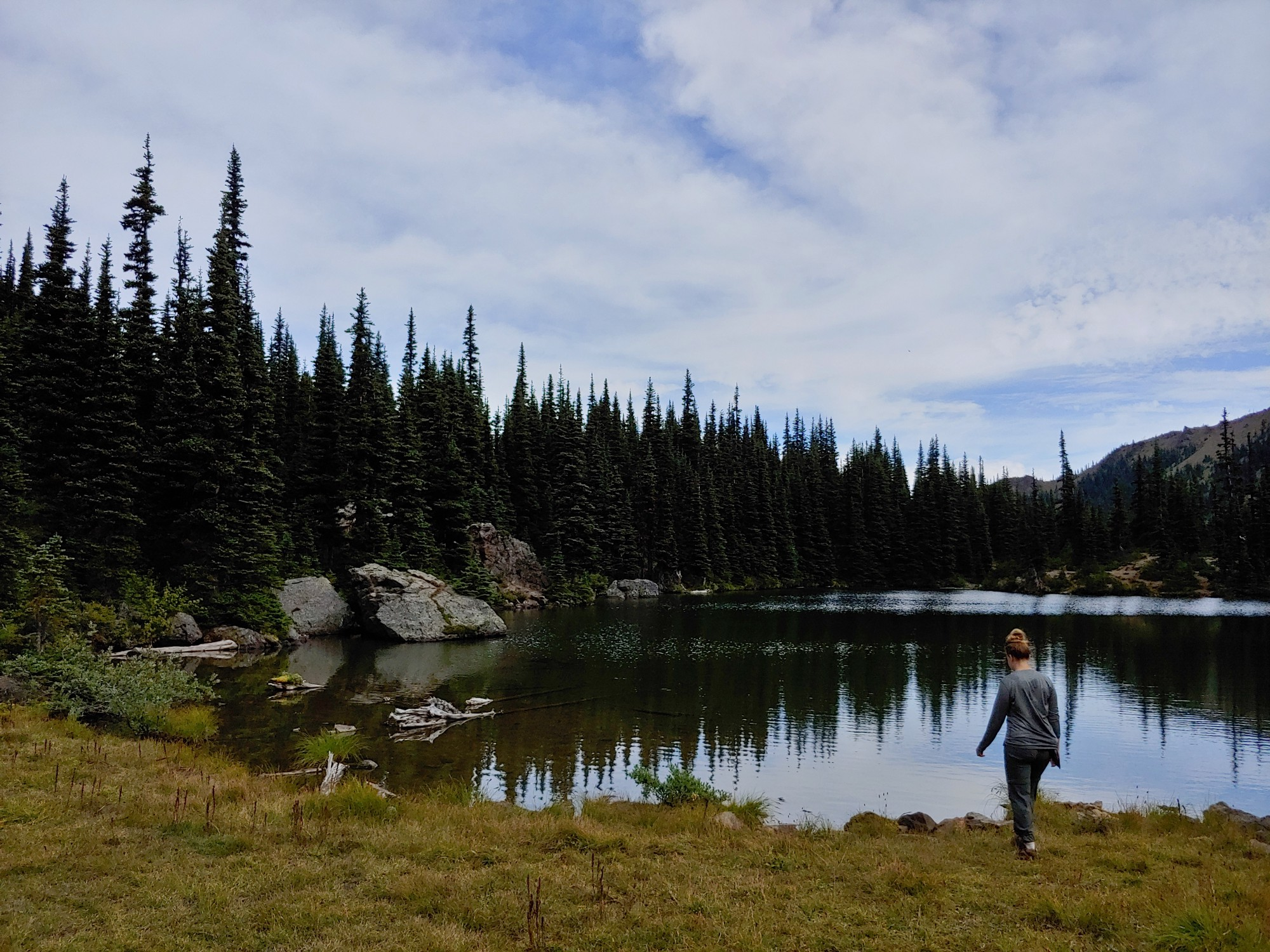 A hiker approaches the shore of Silver Lake in Olympic National Forest.