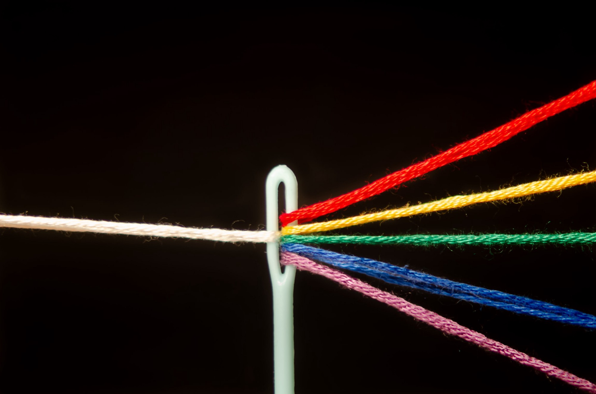 Colored threads passing through the eye of a needle to form one white strand.