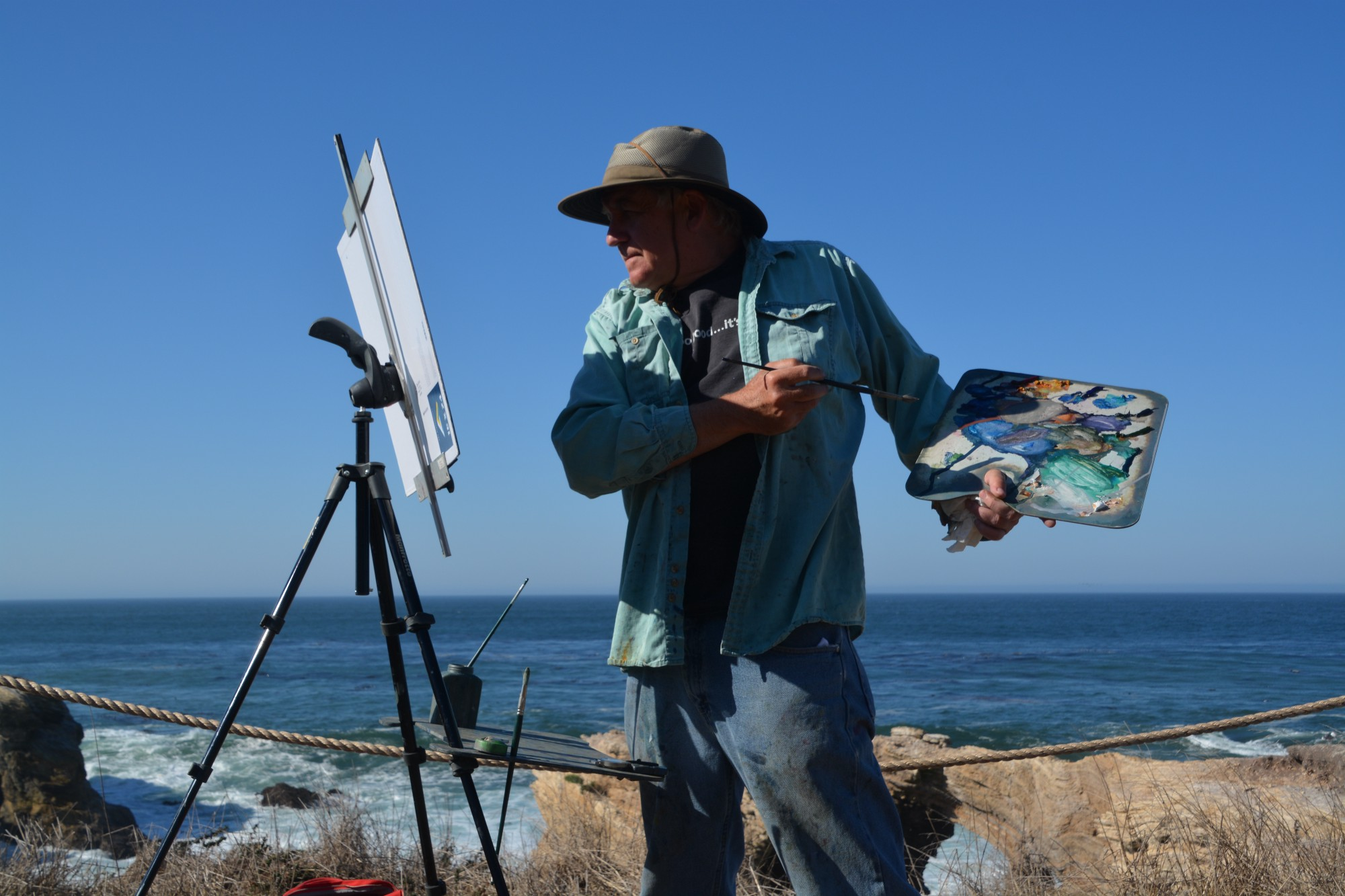 Man along ocean painting on canvas with brush and oil paints.